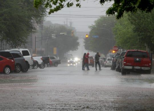 People cross 8th street in the rain Saturday, April 13, 2019.