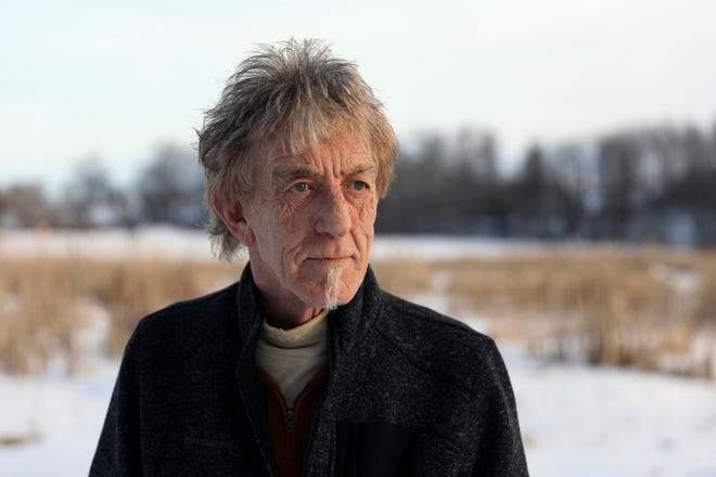 """In this Feb. 15, 2019 photo, Peter Minucci stands on his property in the town of Jefferson, Wisc. Minucci and his wife, Cindy Blanc, are against a proposed wind project near their """"5 acres and janky old farmhouse,"""" as his wife puts it. As working musicians with no pension or retirement, their property is what they've worked for their whole lives, but they say its serenity could be ruined by the wind project."""