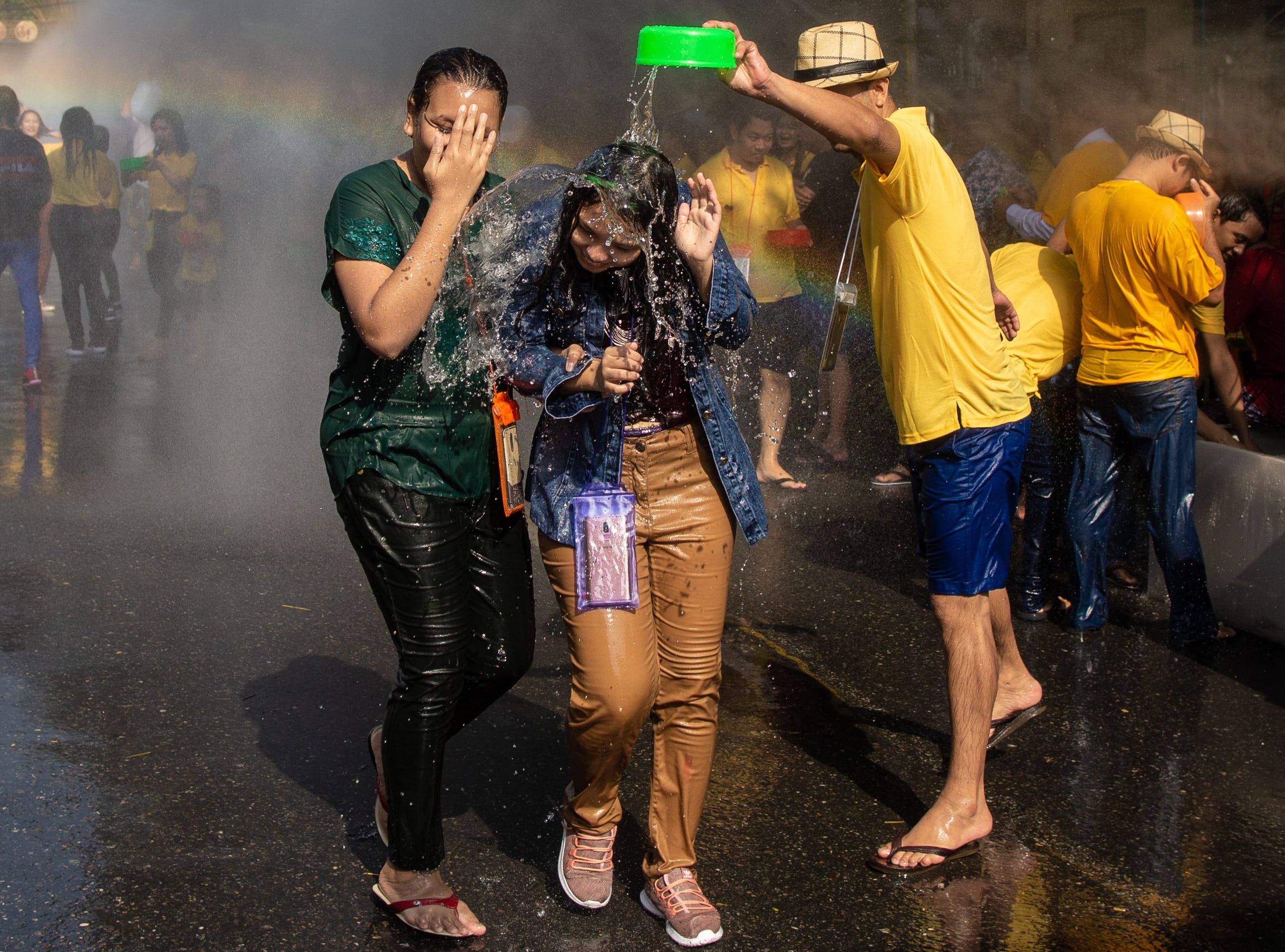 A reveler pours water on two women during celebrations for the Thingyan festival in Yangon.