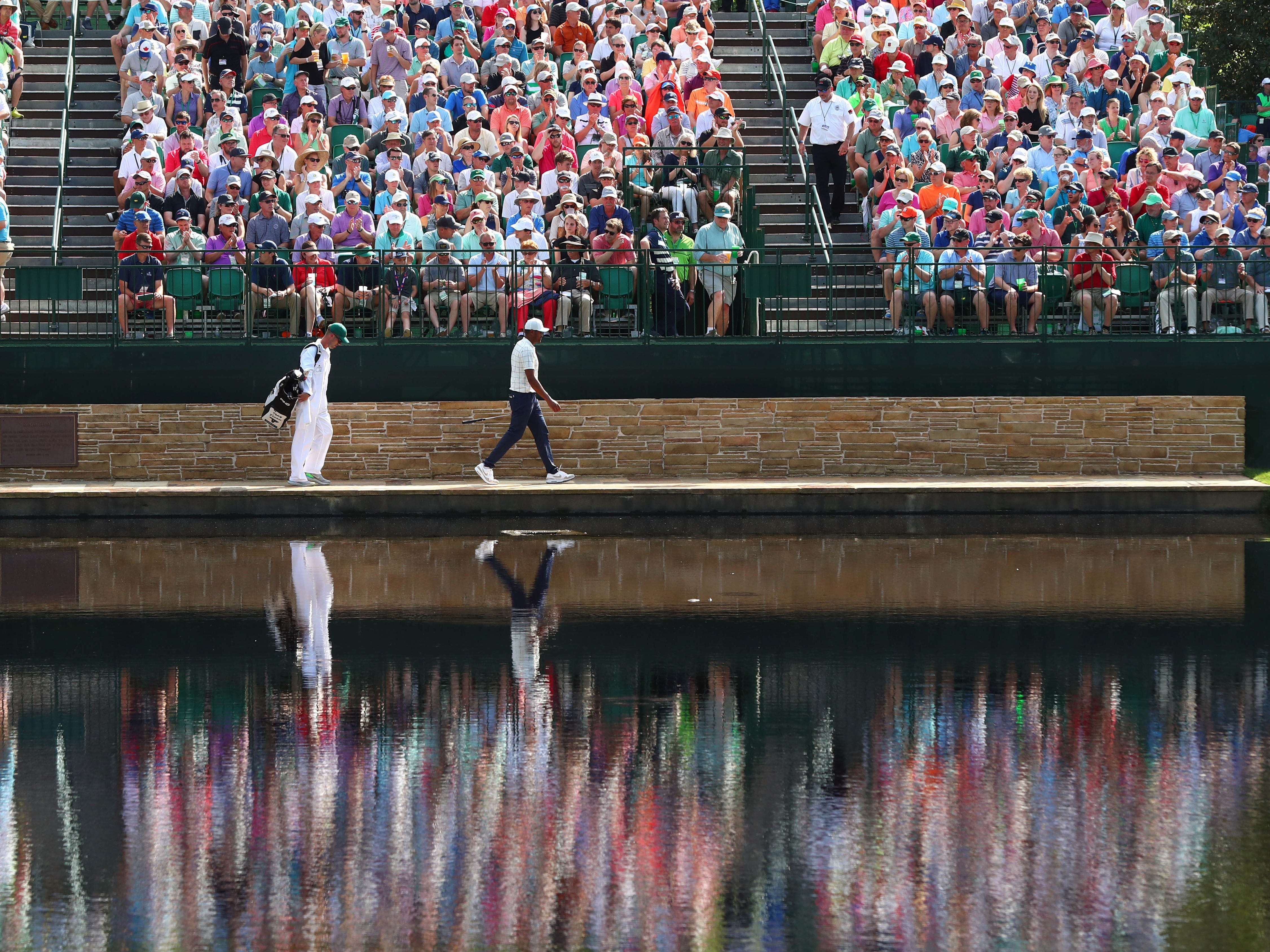 Tony Finau and caddie Gregory Bodine walk across the Sarazen Bridge on the 15th hole during the third round of the Masters.
