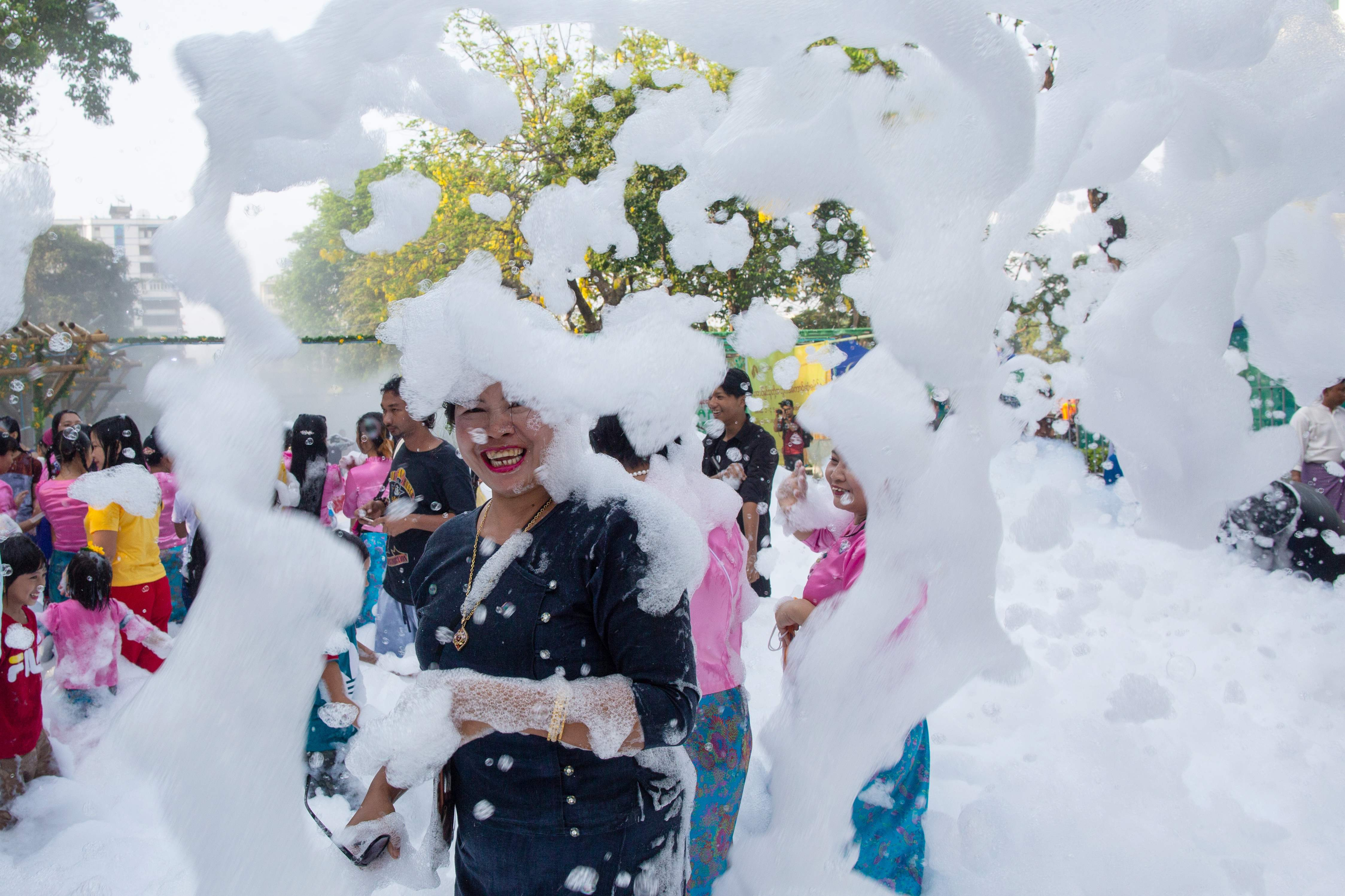 A woman smiles as she is covered in soap suds during celebrations for the Thingyan festival, also known as the Buddhist New Year, in Yangon, Myanmar on April 13, 2019.