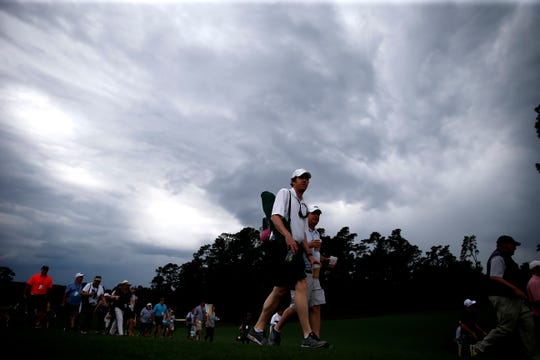 Patrons head for the exits as a weather warning sounds during the second round of the 2019 Masters Tournament at the Augusta National Golf Club in Augusta, Ga. April 12. Forecasters warn another round of storms could hit the tournament Sunday during its final hours.