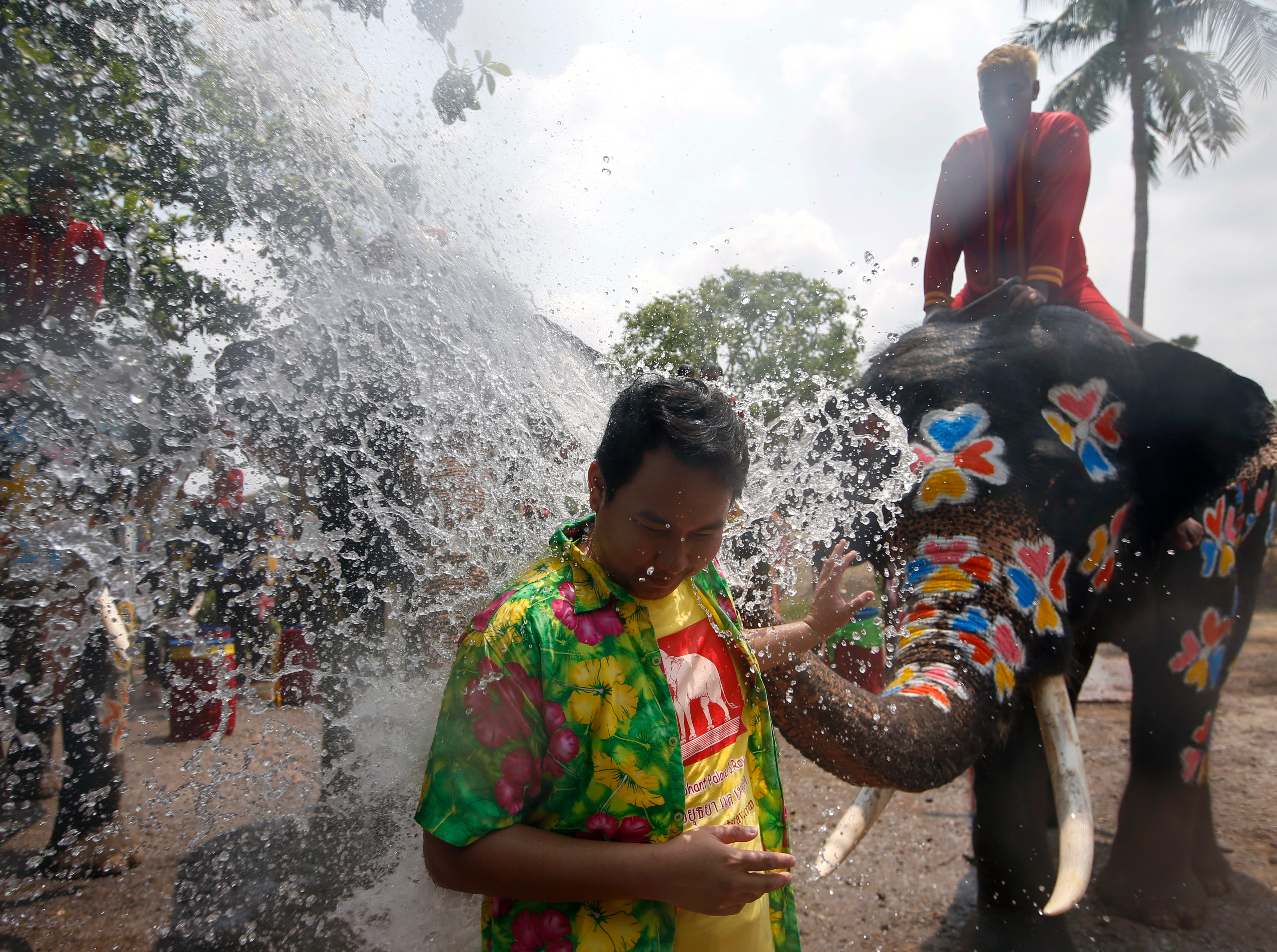A Thai reveler is sprayed with water thrown by an elephant during a preview of the Songkran Festival celebration, also known as the Water Festival, in the city of Ayutthaya, Thailand on April 11, 2019.