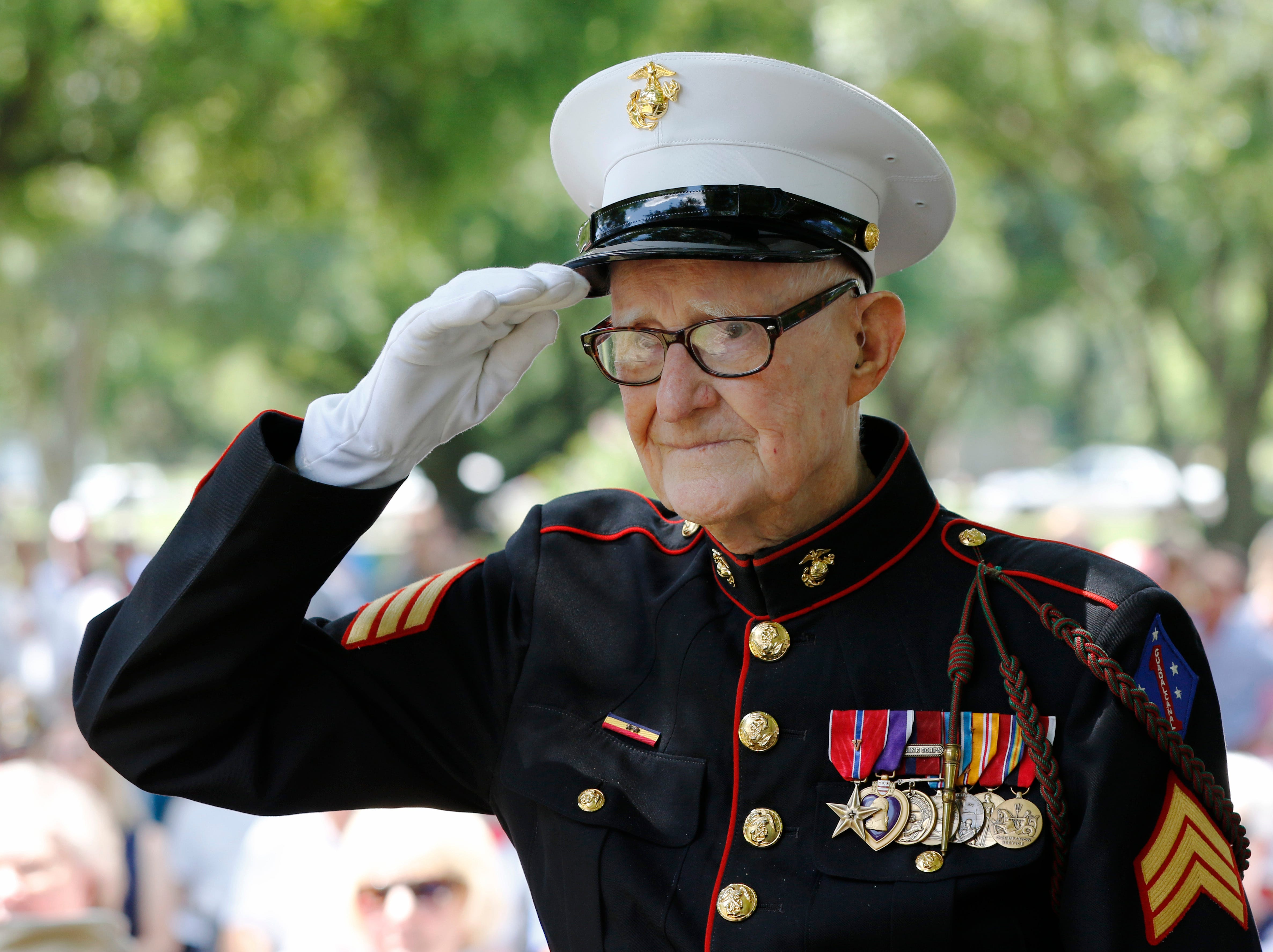 """In a May 30, 2016 photo, U.S. Marine veteran R. V. Burgin, 93, salutes during the 76th Annual Memorial Day Service at Restland Memorial Park in Dallas. Burgin, whose book about grueling jungle combat during WWII became a basis for the HBO miniseries """"The Pacific"""" died April 6, 2019 at his home in Texas. He was 96."""