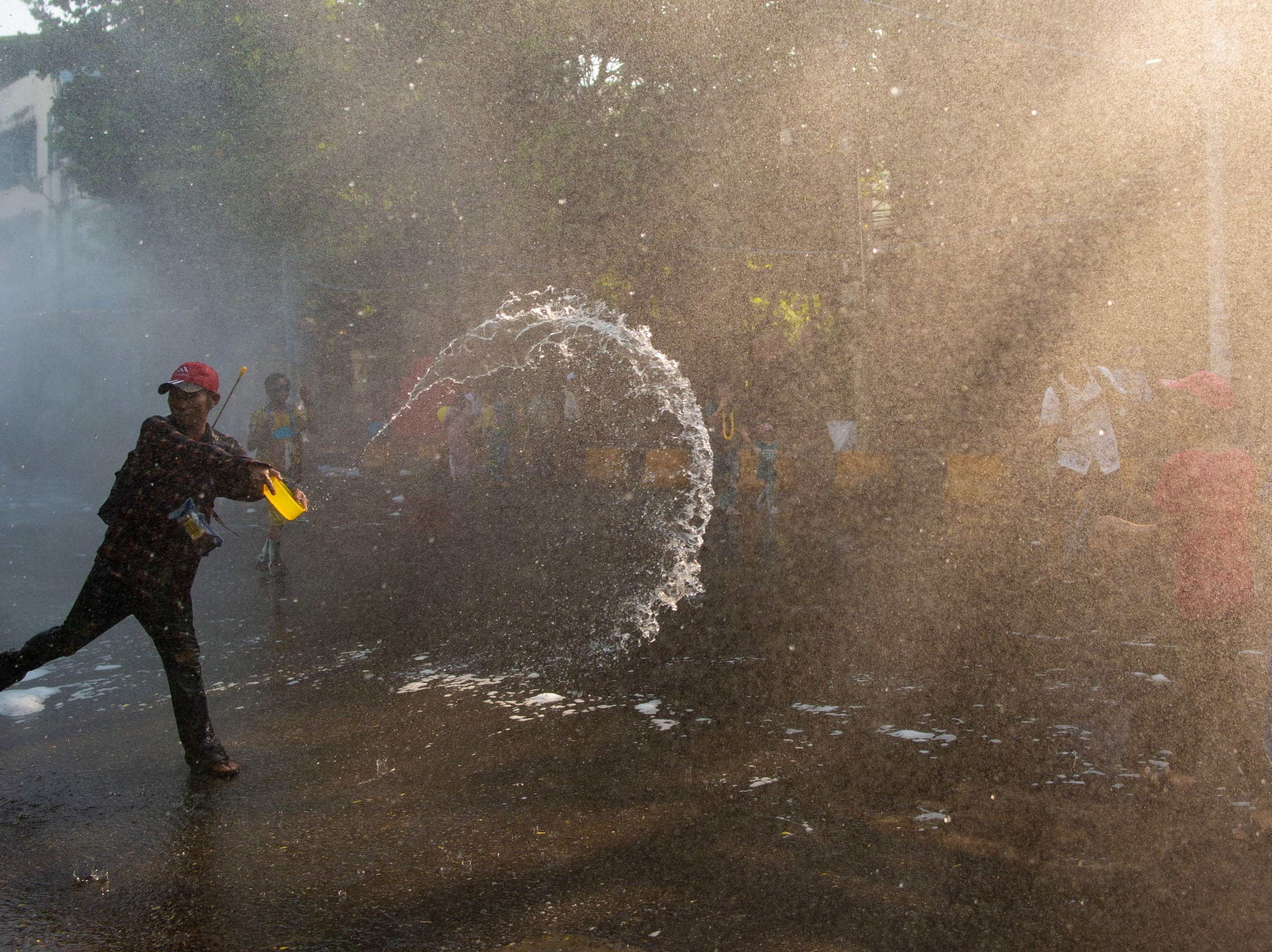 A man throws water during celebrations for the Thingyan festival in Yangon on April 13, 2019.