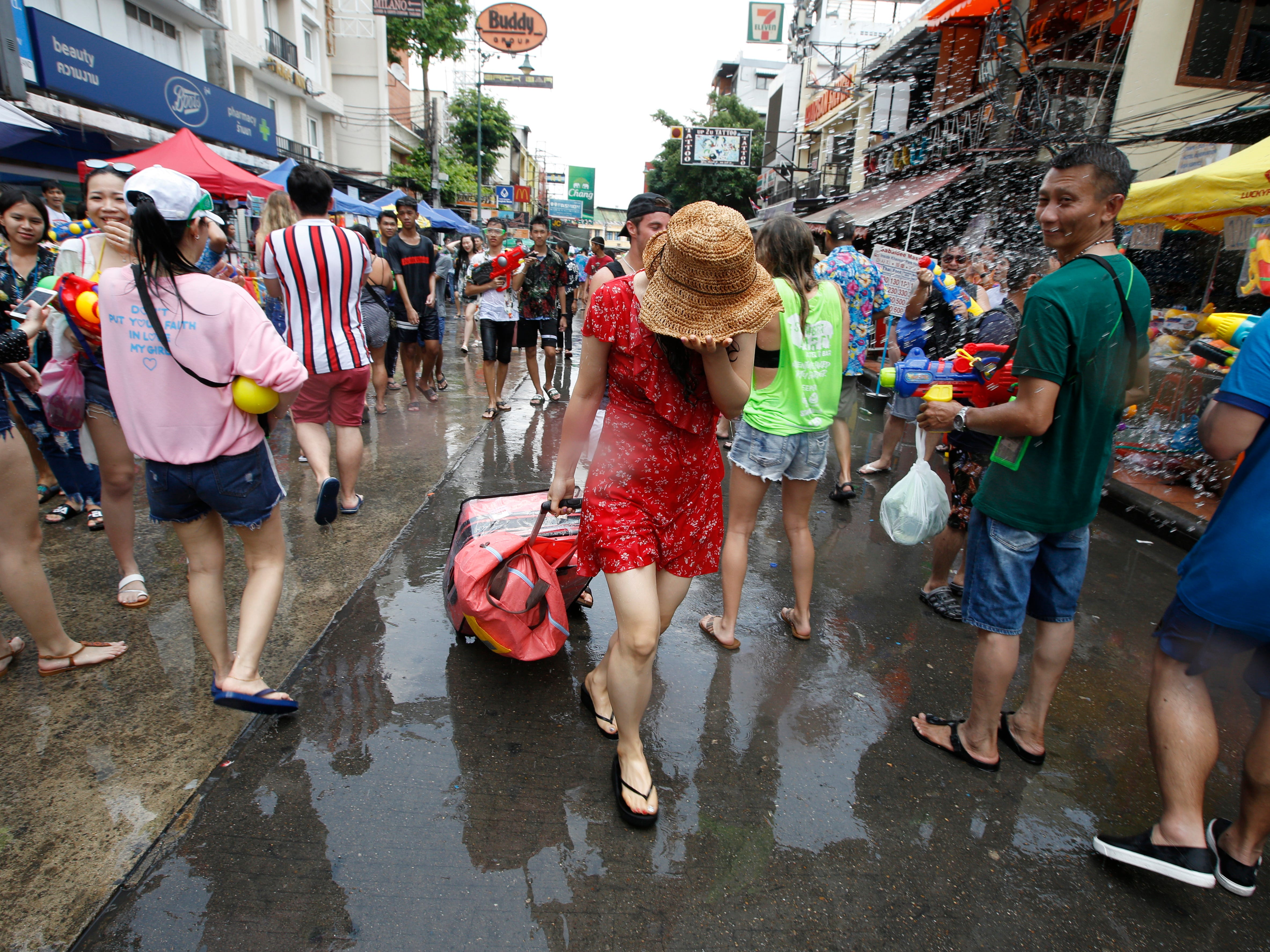 A tourist woman is soaked as she arrives on the popular tourist strip of Khao San road during the Songkran Festival, the celebrations on Thai traditional New Year, also known as the water festival in Bangkok, Thailand on April 13, 2019. Songkran Festival is held to mark the Thai traditional New Year falling annually on 13 April, and it is celebrated throughout the Kingdom with splashing water and putting powder on each others faces as a symbolic sign of cleansing and washing away the sins from the past year.