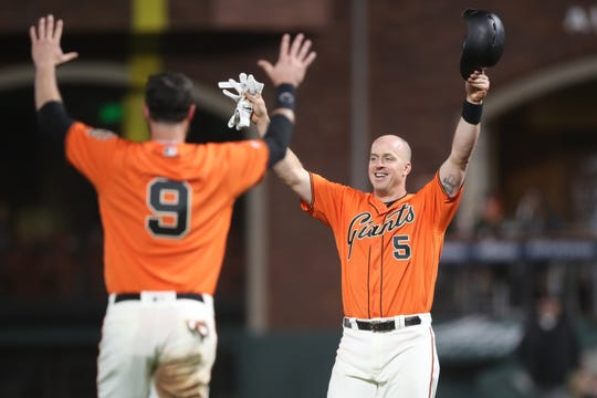 April 12: San Francisco Giants catcher Erik Kratz (5) and first baseman Brandon Belt (9) celebrate after their 18-inning victory against the Colorado Rockies at Oracle Park.