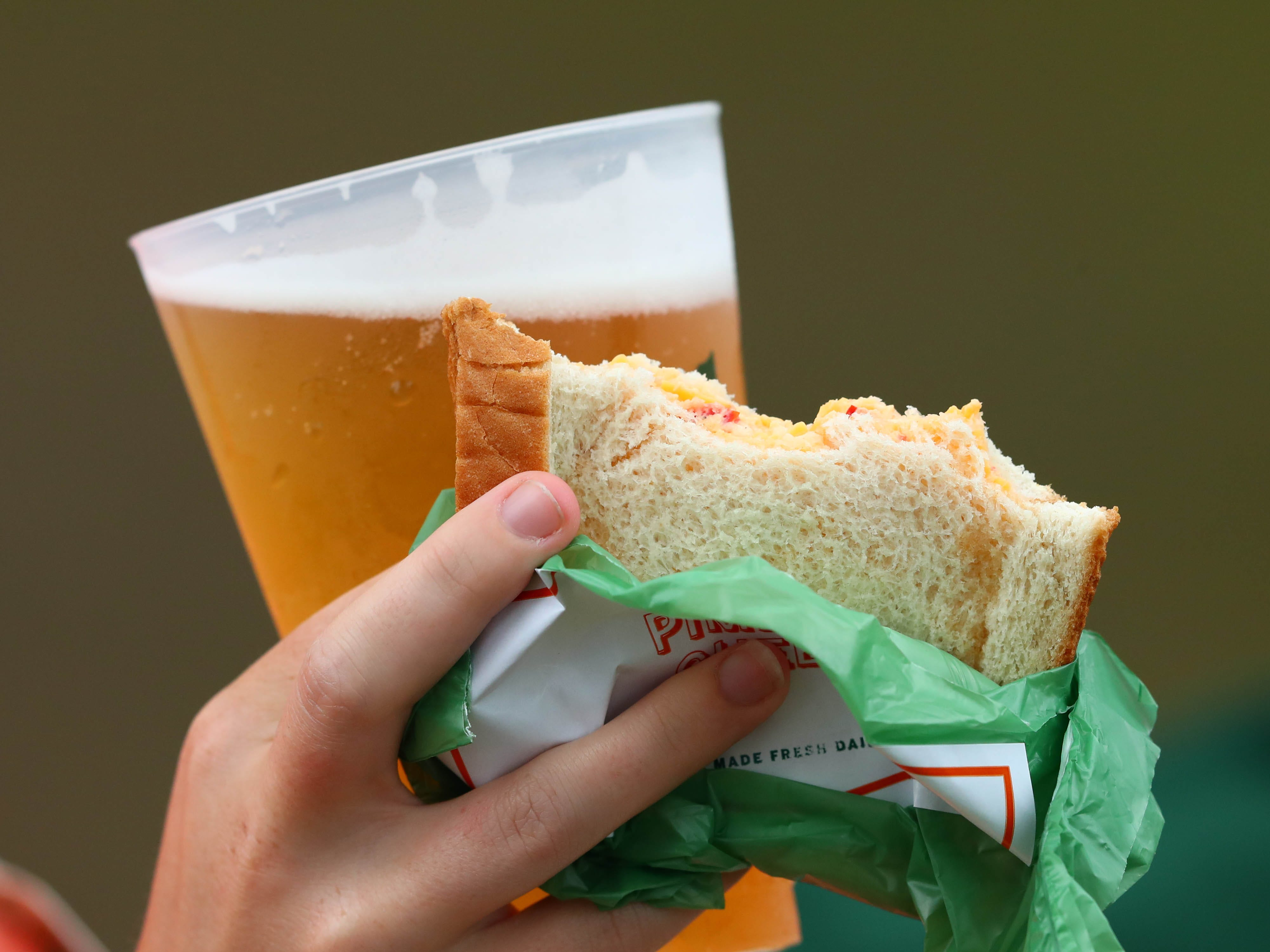 A patron holds a pimento cheese sandwich and beer during the third round of the Masters.