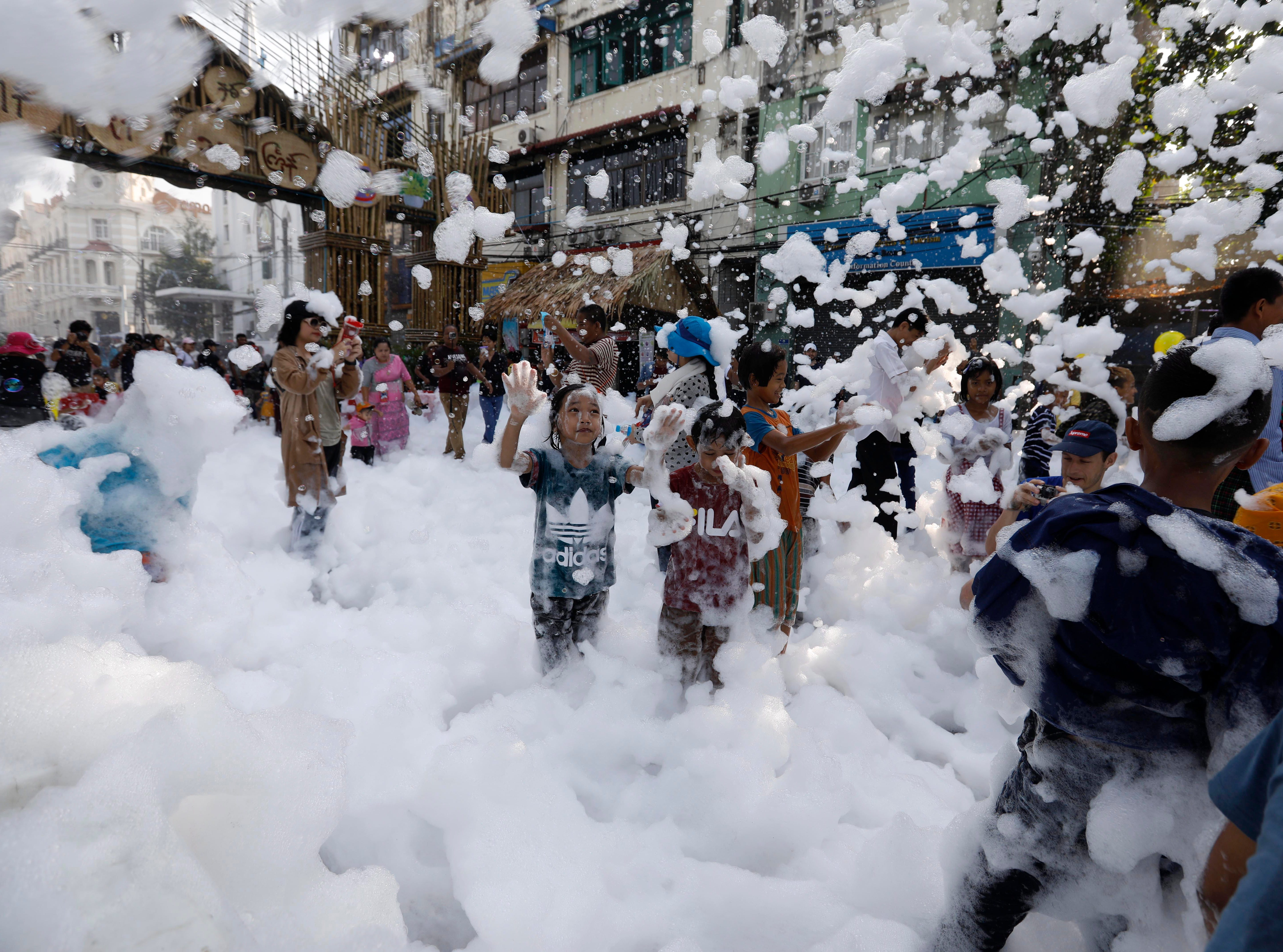 Children play with soap foam during Thingyan Water Festival in Yangon, Myanmar on April 13, 2019. The annual water festival, known as Thingyan, features large groups of people congregating to celebrate the by splashing water and throwing powder at each other's faces as a symbol of cleansing and washing away the sins from the old year. It marks the start of the traditional New Year and is similarly celebrated in countries such as Myanmar, Thailand, Laos, and Cambodia.