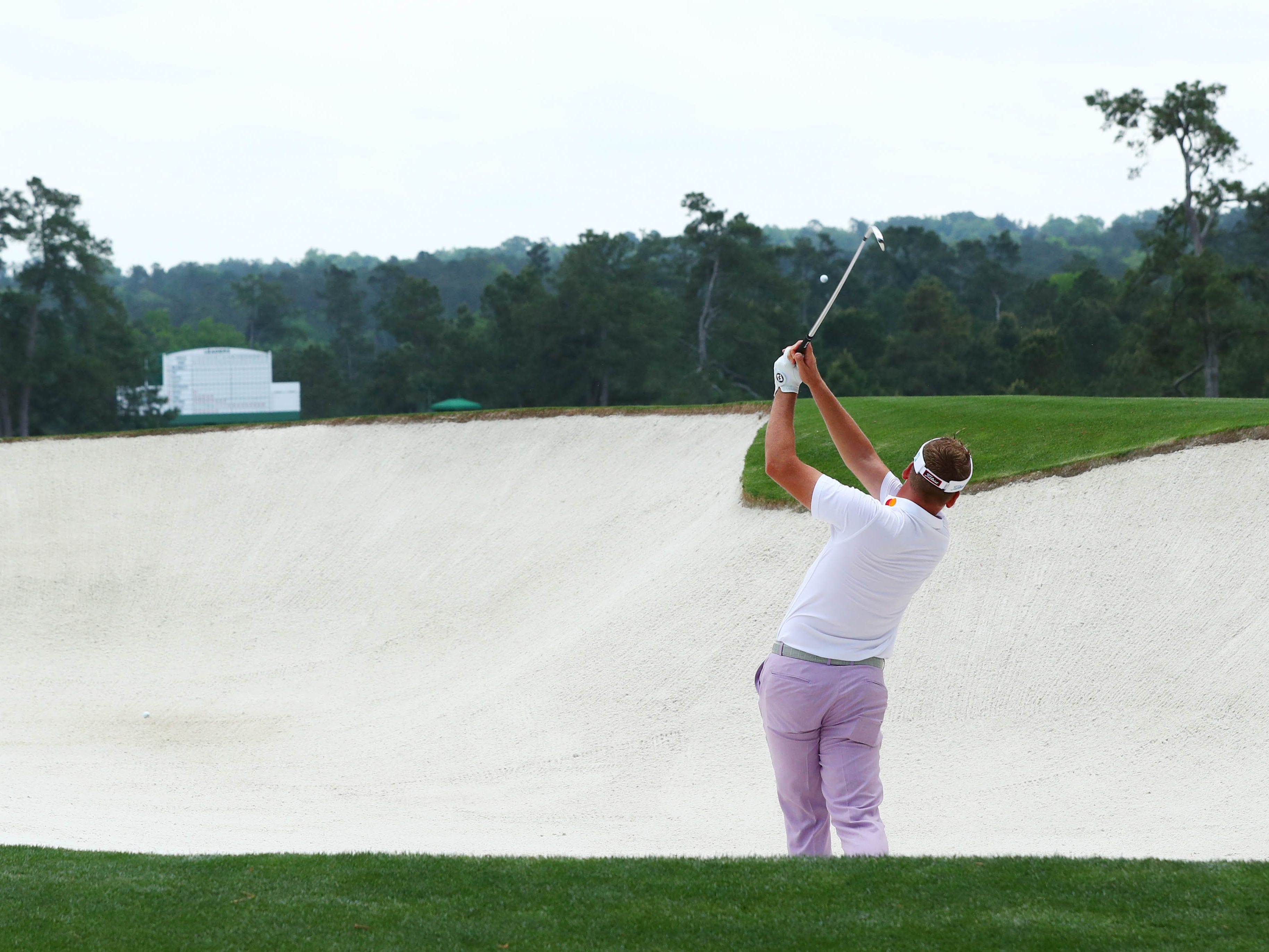 Ian Poulter hits out of a bunker on the second hole during the third round of the Masters.