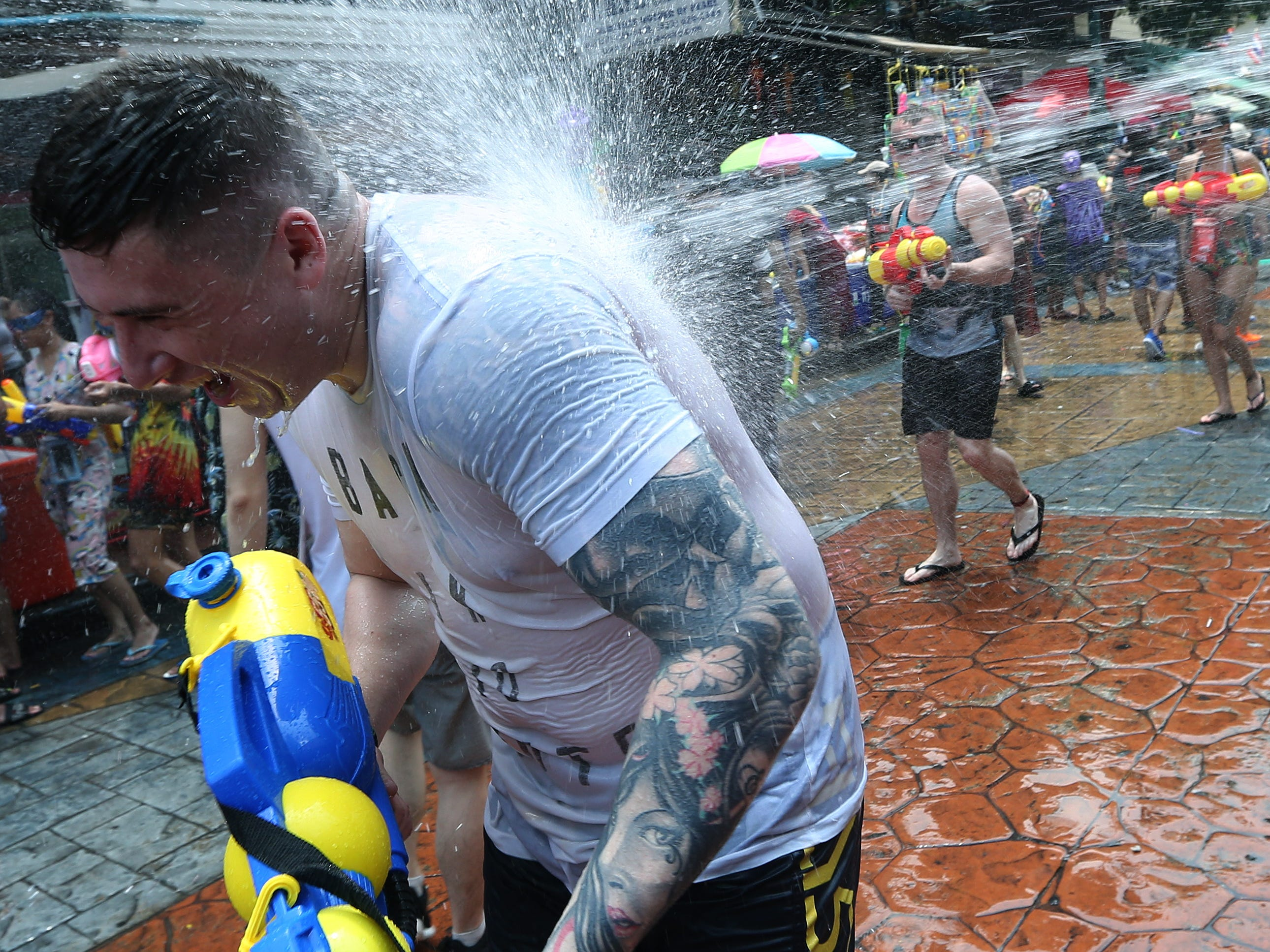 A reveler is doused in a water gun battle as they join the Songkran Festival, the celebrations on Thai traditional New Year in Bangkok, Thailand on April 13, 2019.