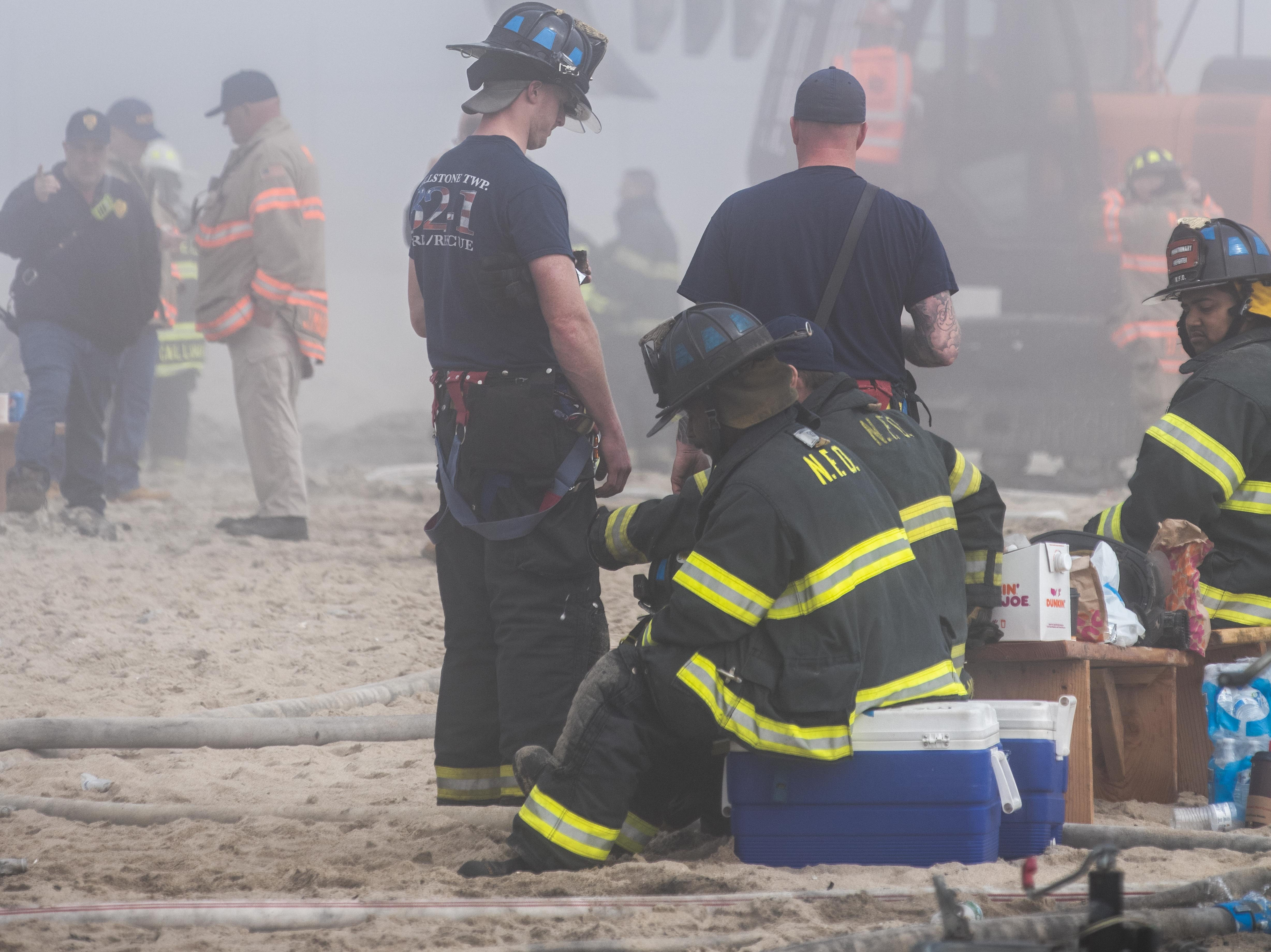 A heavy fog blankets the aftermath of The Dunes Cafe Fire on the Ocean Grove North Pavillion . Firefighters continue to hose down the smoldering remains and crews begin to move debris. Photo/James J. Connolly/Correspondent 4/14/19