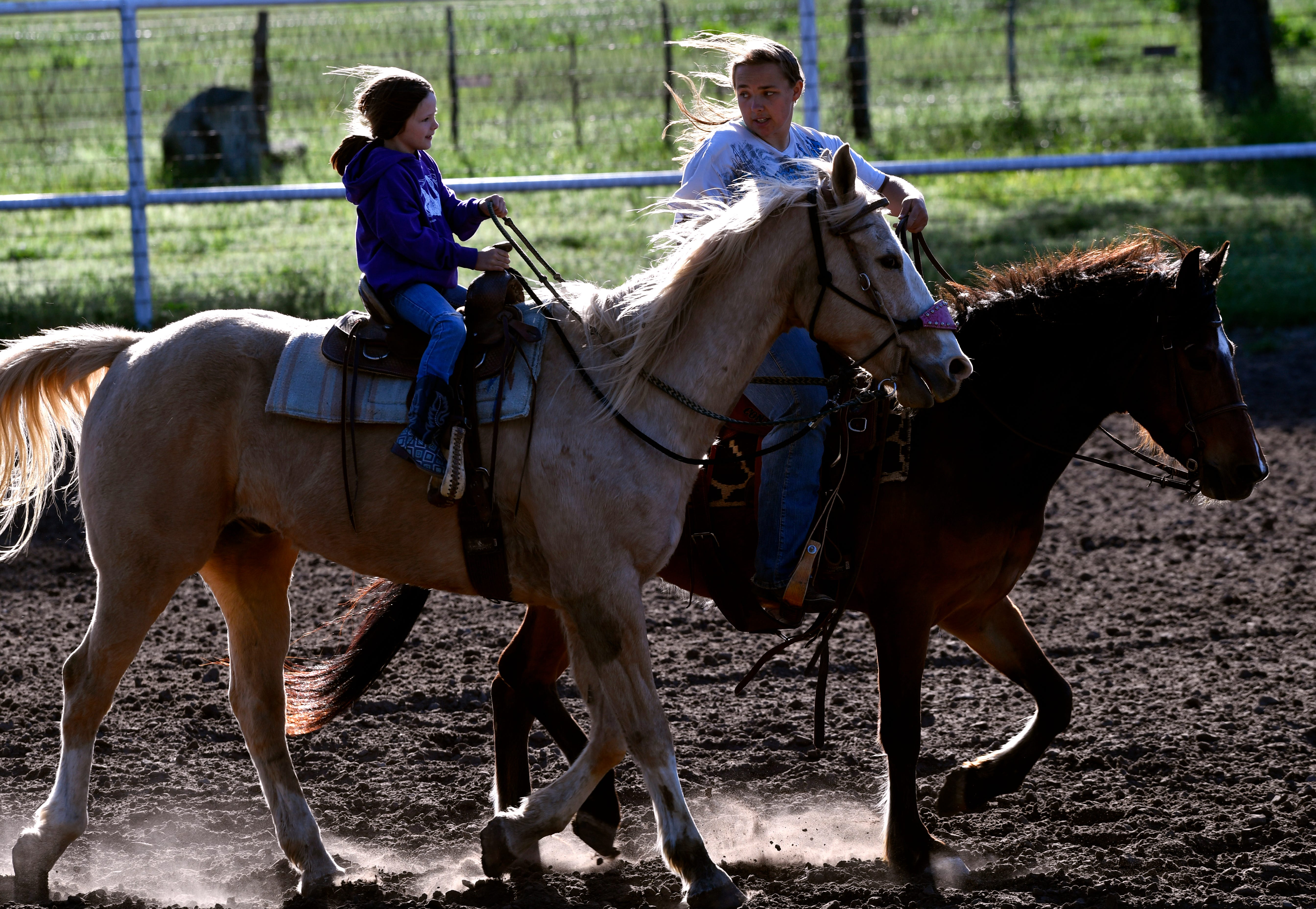Cayden Frazier coaches Cami Stout, 7, around the barrels Thursday at the Comanche Rodeo Arena. It was Cami's first time on a course like this.