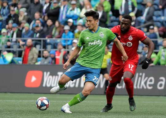 Seattle Sounders midfielder Kim Kee-Hee, left, kicks the ball away from Toronto FC forward Jozy Altidore (17) during the first half of an MLS soccer match, Saturday, April 13, 2019, in Seattle.