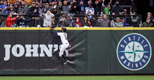 Seattle Mariners center fielder Mallex Smith and fans watch the home run ball of Houston Astros' Jose Altuve in the fifth inning of a baseball game Saturday, April 13, 2019, in Seattle.