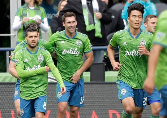 Seattle Sounders forward Will Bruin, center, walks with teammates Victor Rodriguez, left, and Kim Kee-Hee, right, after Bruin scored a goal against Toronto FC during the first half of an MLS soccer match, Saturday, April 13, 2019, in Seattle.