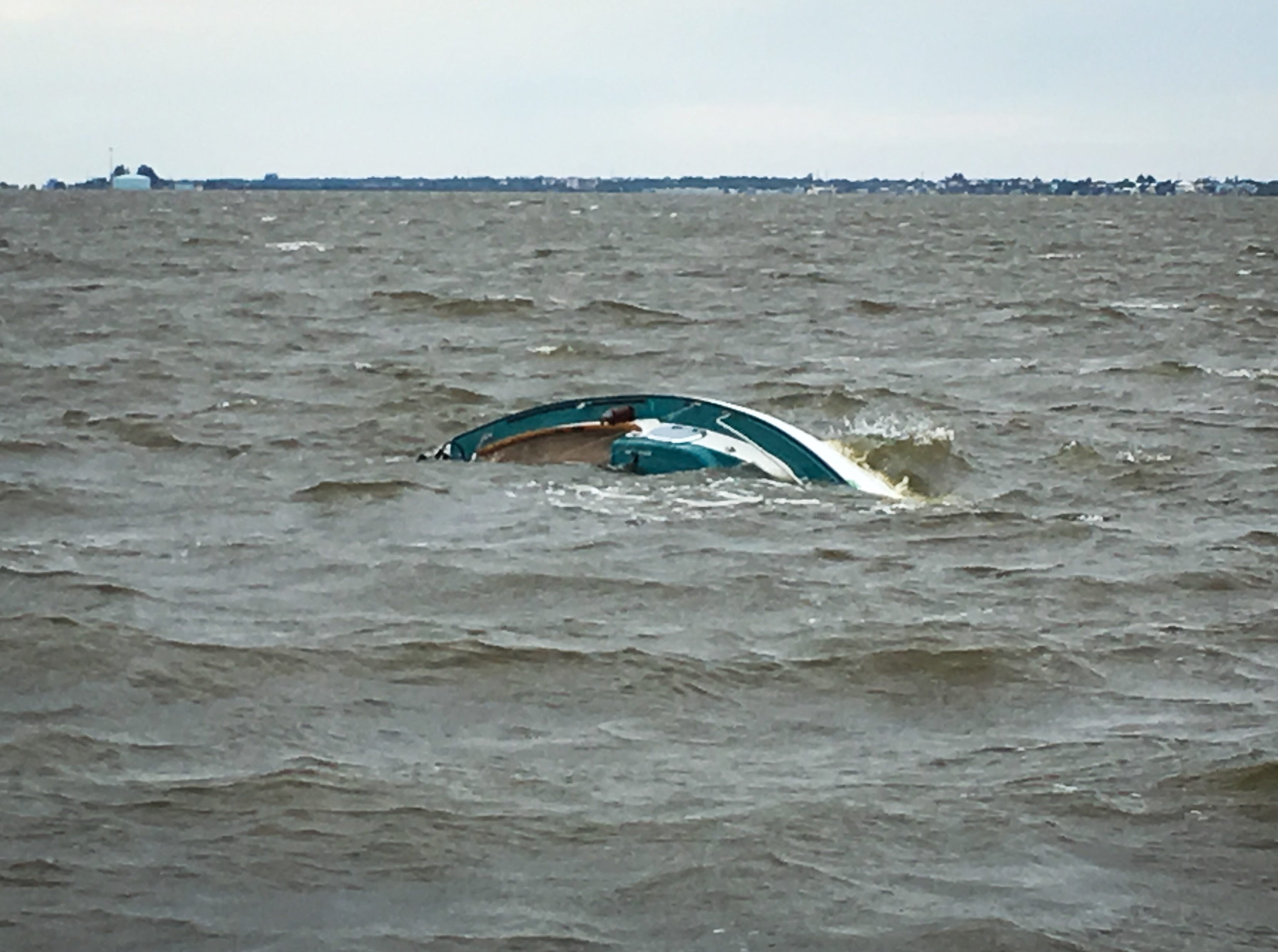 The boat  flipped over and partially bobbed just above the choppy waves of the river.