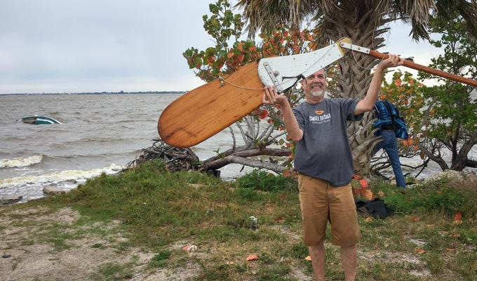 Dr. Chris Edwards,  owner of the 20-foot boat which capsized in the Banana River Sunday, April 14, 2019, holds its rudder in his hands.