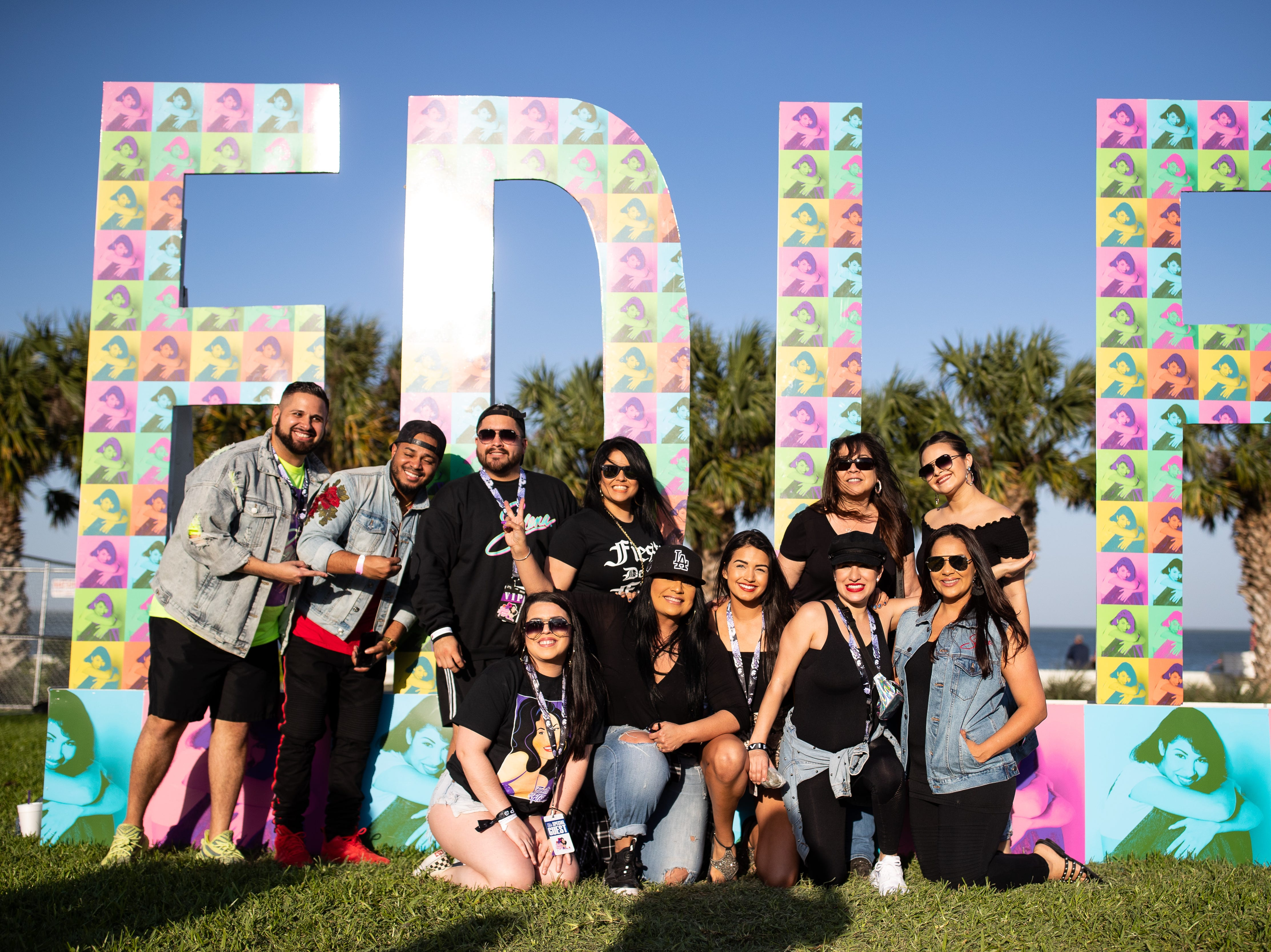 Suzette Quintanilla takes a photo with a group of people at the FDLF sign during the second day of Fiesta de la Flor on Saturday, April 13, 2019.