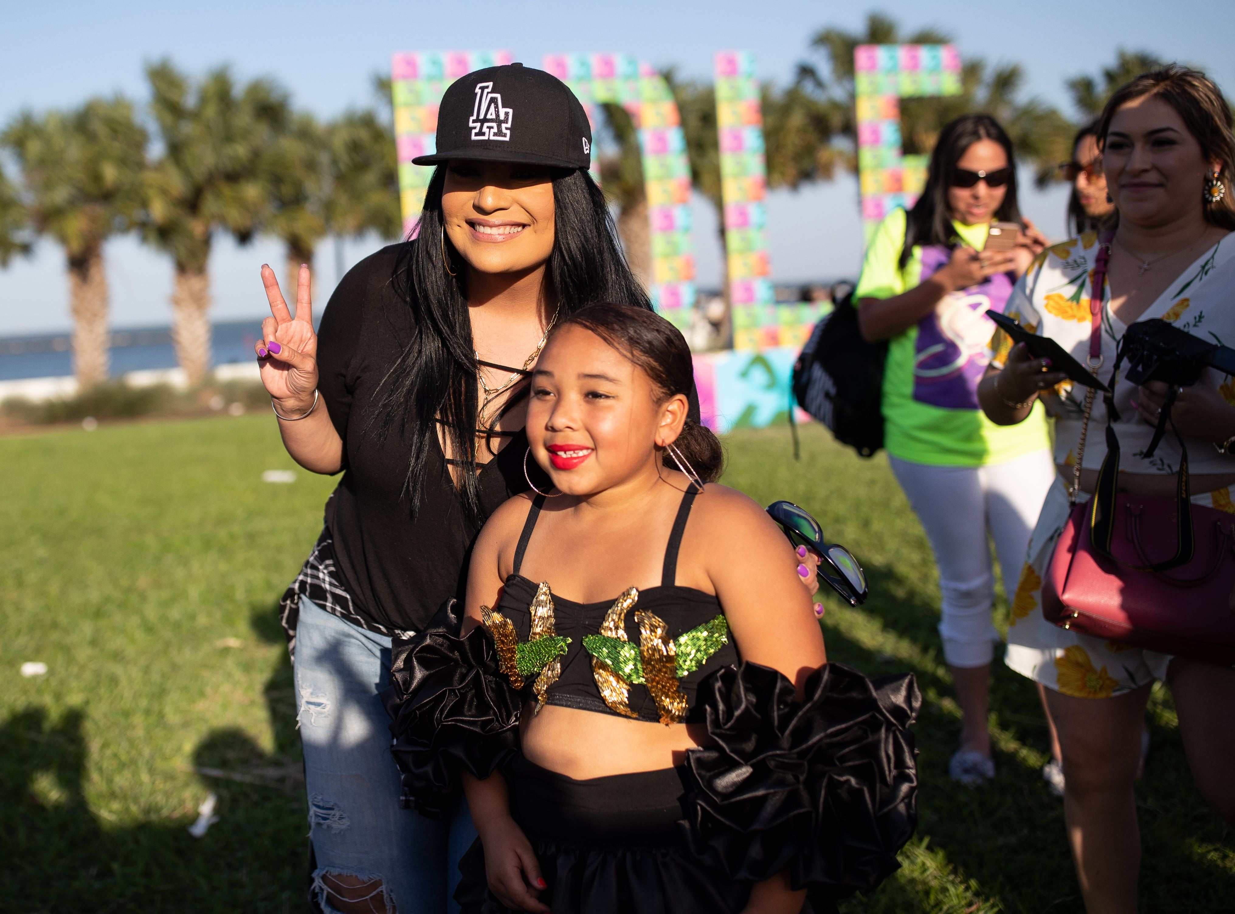 Suzette Quintanilla takes a photo a young girl dressed as Selena in the crowed during the second day of Fiesta de la Flor on Saturday, April 13, 2019.