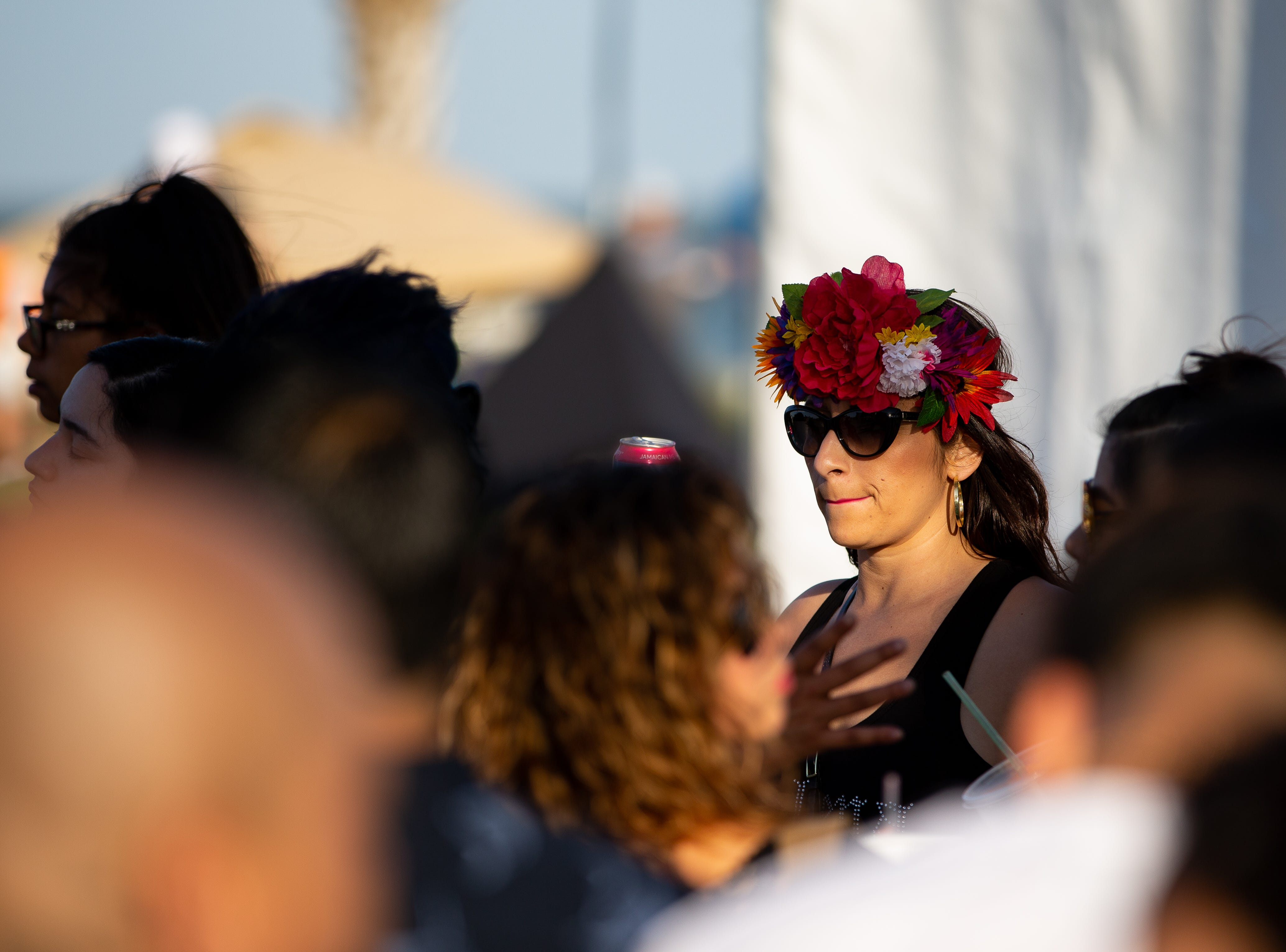 A women waits inline with a slower crown at the FDLF sign during the second say of Fiesta de la Flor on Saturday, April 13, 2019.