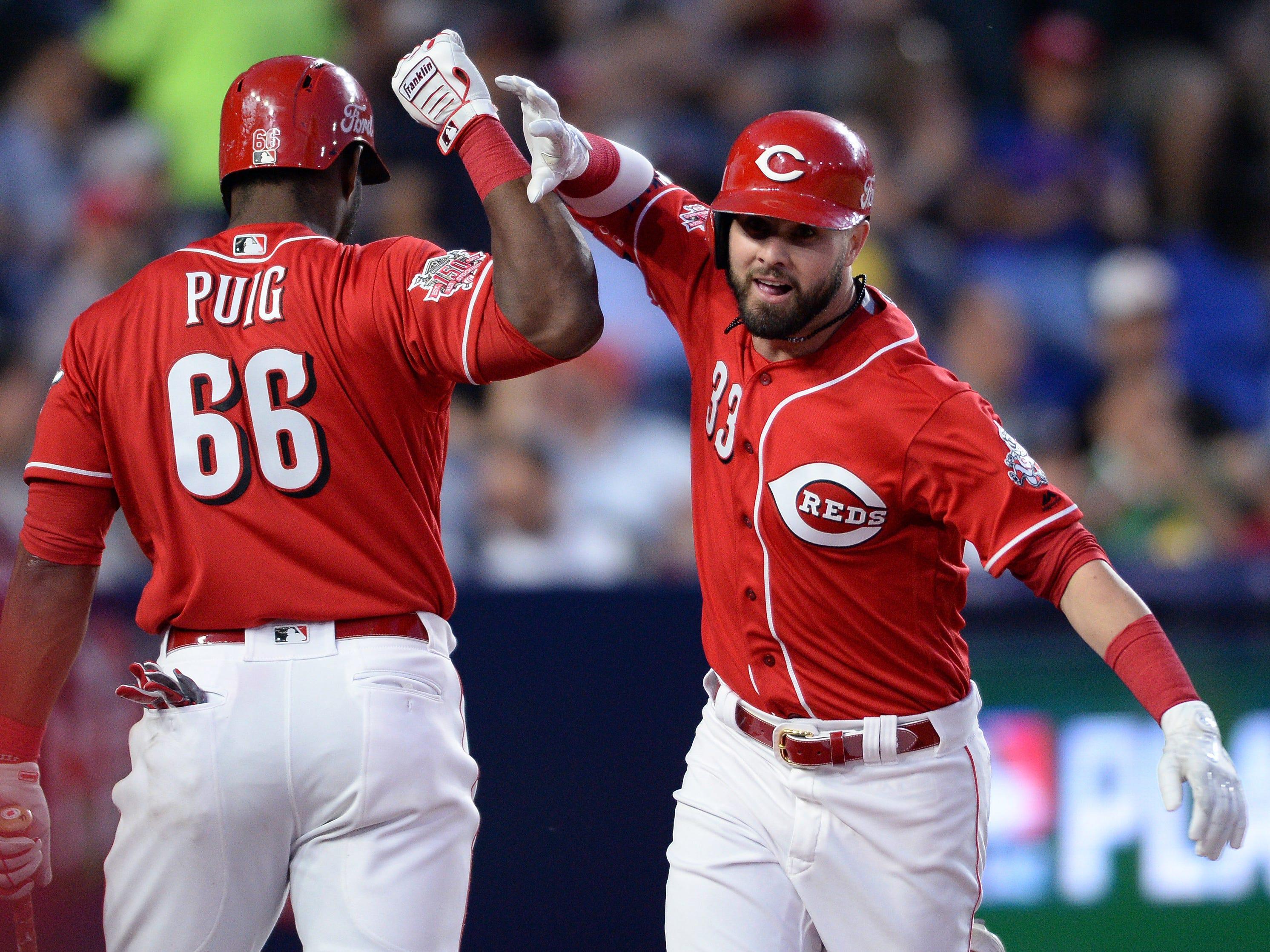 Cincinnati Reds left fielder Jesse Winker (33) is congratulated by right fielder Yasiel Puig (66) after hitting a home run during the sixth inning at Estadio de Beisbol Monterrey.