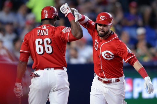 Cincinnati Reds left fielder Jesse Winker (33) is congratulated by right fielder Yasiel Puig (66) after hitting a home run during the sixth inning at Estadio de Beisbol Monterrey.