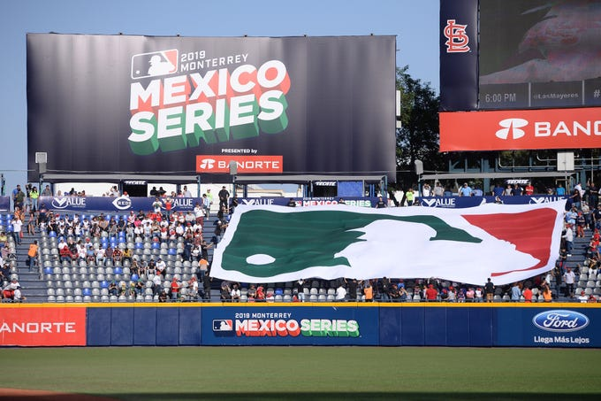 A MLB logo banner with Mexico's flag colors is displayed in left field prior to the game between the Cincinnati Reds and the St. Louis Cardinals at Estadio de Beisbol Monterrey.
