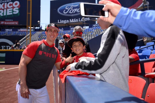 Apr 14, 2019; Monterrey, MEX; Cincinnati Reds relief pitcher Michael Lorenzen (21) takes a photograph with a fan before the game against the St. Louis Cardinals at Estadio de Beisbol Monterrey. Mandatory Credit: Orlando Ramirez-USA TODAY Sports