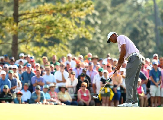 Tiger Woods putts on the 17th green during the third round of The Masters golf tournament at Augusta National Golf Club.