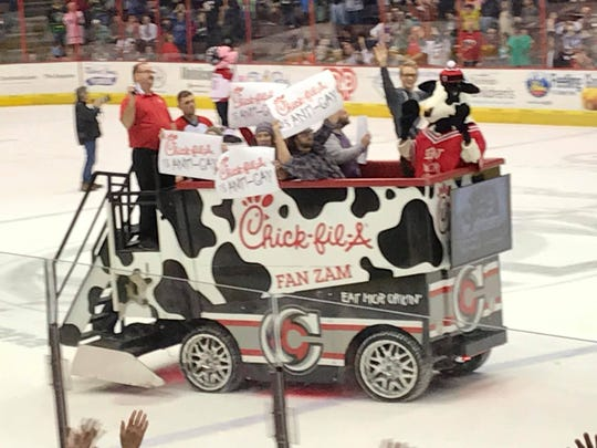 "People hold up ""Chick-fil-A is ANTI-GAY"" signs aboard the fast-food company's ""Fan Zam"" Zamboni on the ice at the April 13, 2019 Cincinnati Cyclones hockey game at US Bank Arena."
