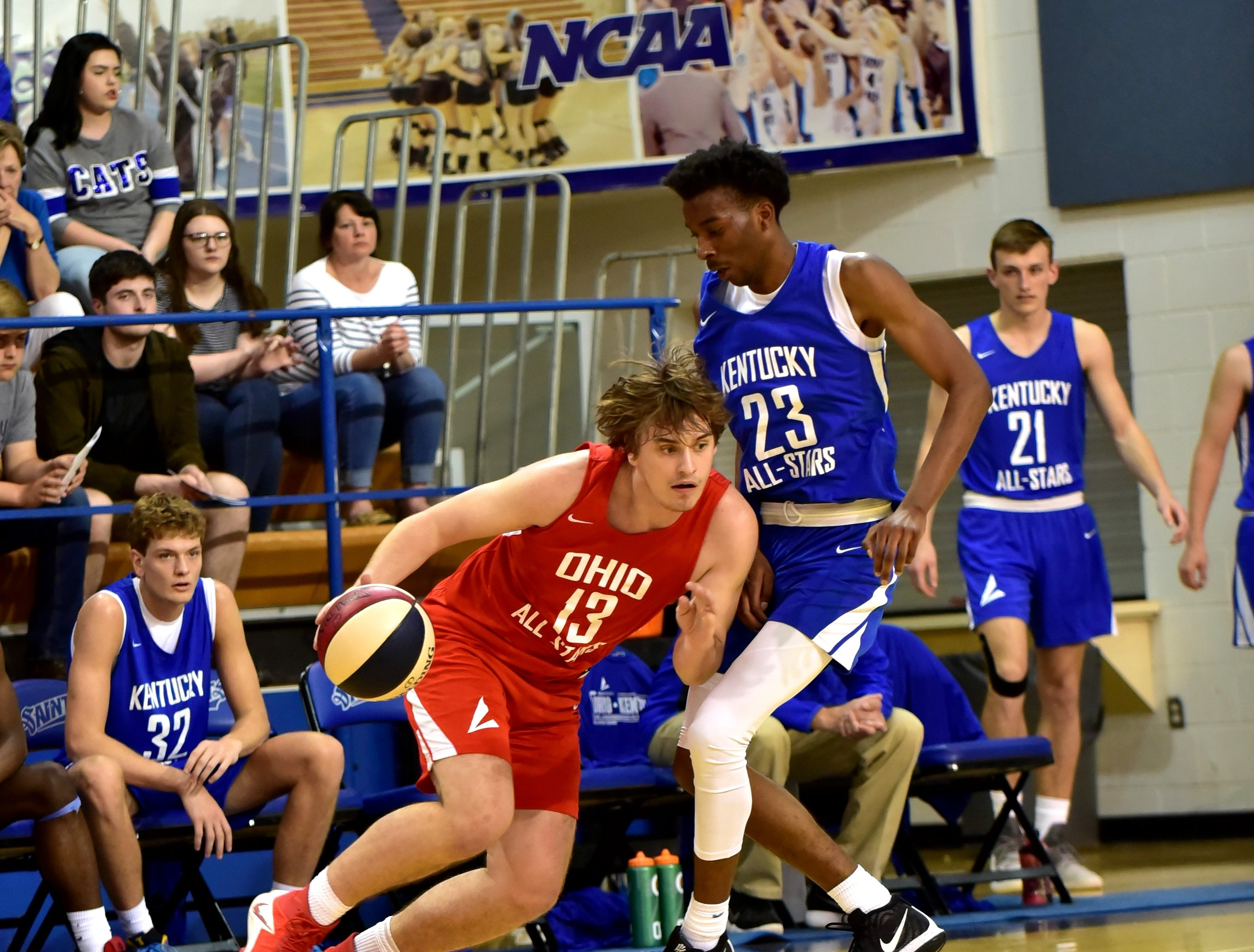 Mason Darby (13) of Oak Hill dribbles out of trouble for the Ohio boys team as Darius Osborne from Pleasure Ridge Park of the Kentucky boys team offers defense at the 28th Annual Ohio-Kentucky All Star Games played at Thomas More University, April 13, 2019