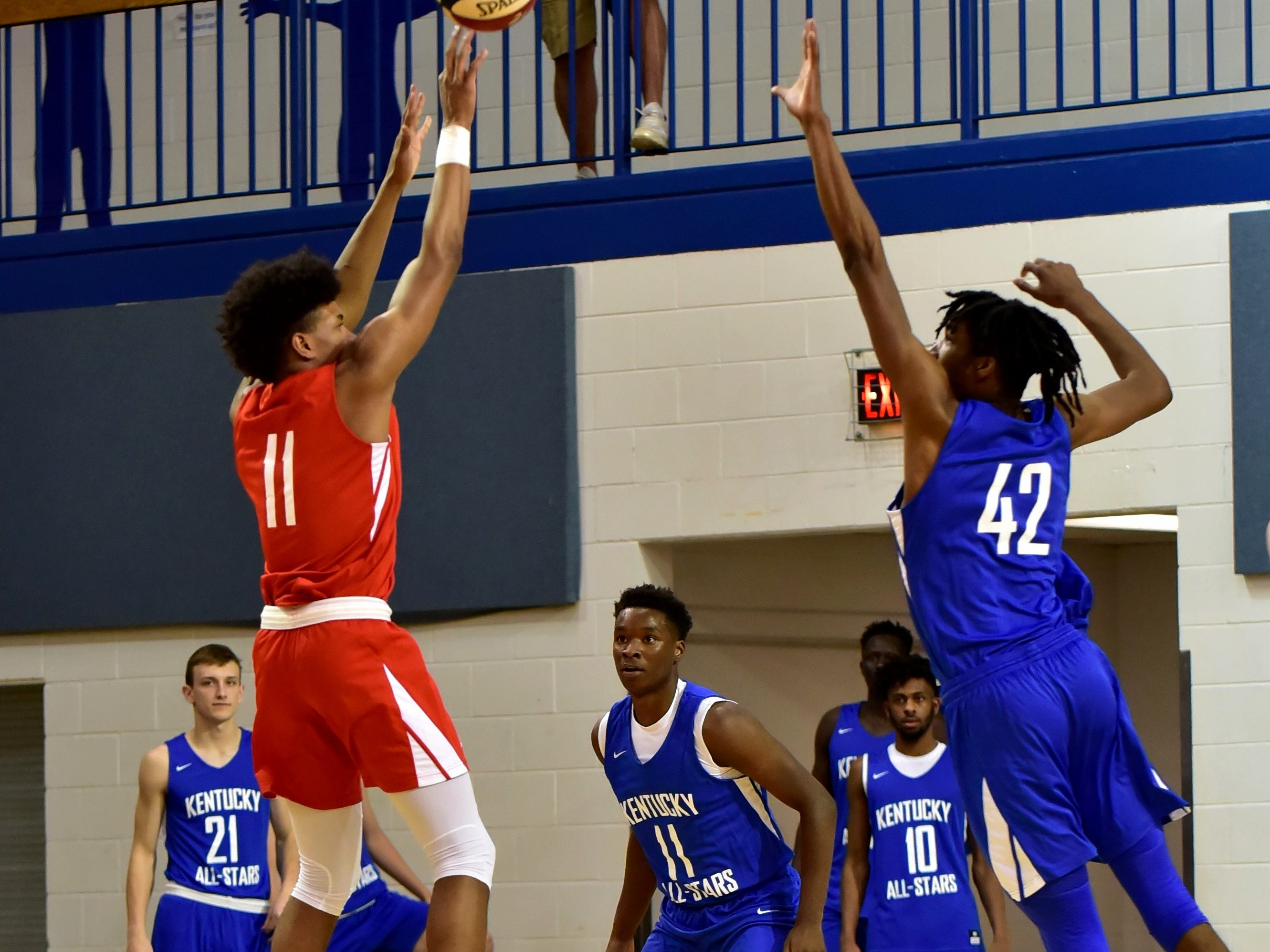 Miles McBride (11) of Moeller fires home a jump shot for the Ohio boys team as Dieonte Miles of Walton-Verona offers defense for the Kentucky boys team at the 28th Annual Ohio-Kentucky All Star Games played at Thomas More University, April 13, 2019