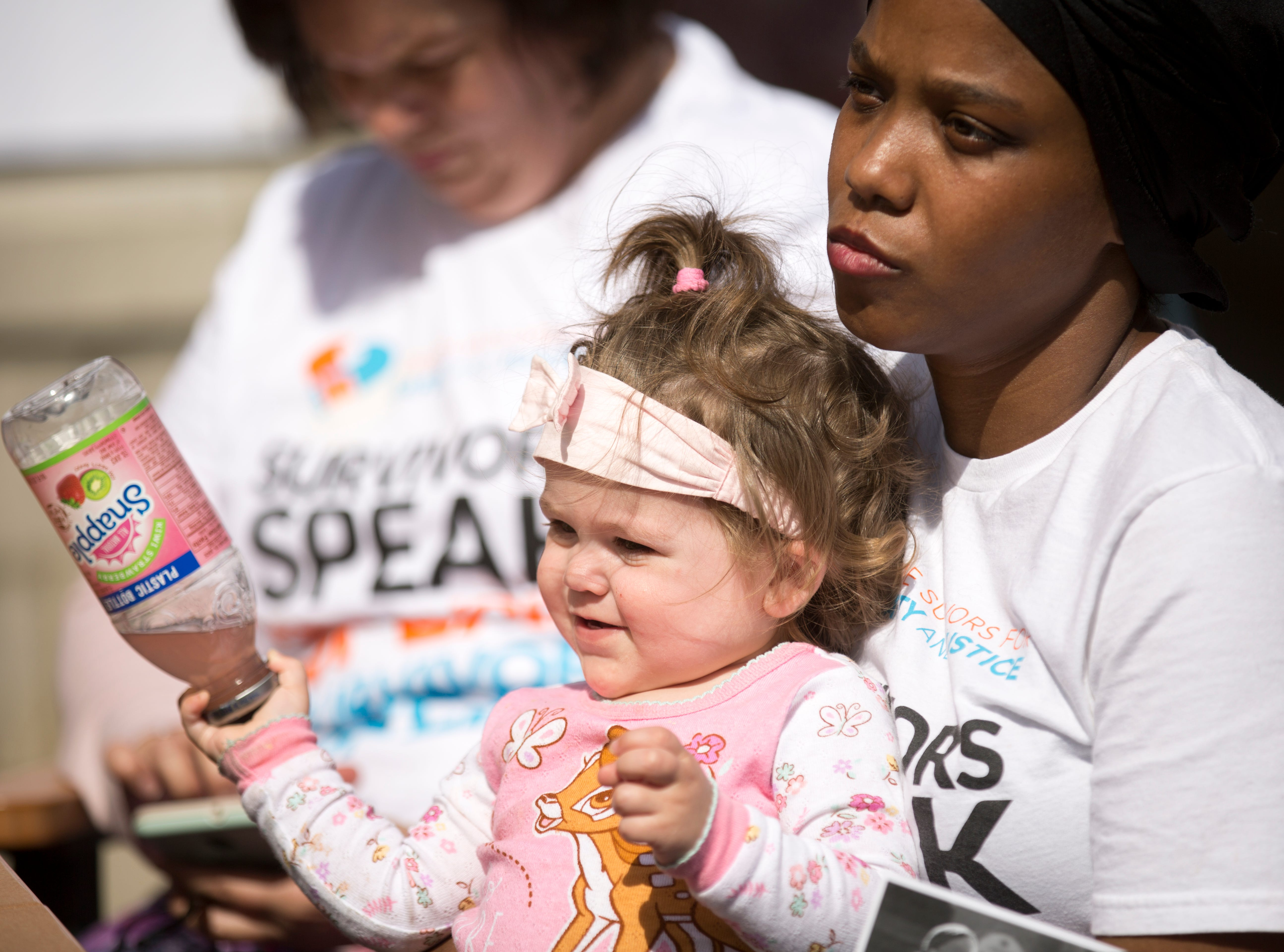 Megan Stewart, of Springfield, Ohio, holds her friend, Haleigh Young's child, Marleigh, 1, during the healing vigil at St. Paul Village in Madisonville, Saturday, April 13. The Cincinnati chapter of Crime Survivors for Safety and Justice were taking part in the national healing vigil day that gave survivors an opportunity to share their story. Stewart, herself a survivor said, 'In order for me to truly believe that I'm a survivor, I have to let go and understand that I'm no longer in that situation anymore.'