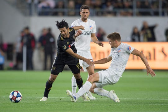 FC Cinncinati defenseman Nick Hagglund (14) attempts to tackle the ball away from Los Angeles FC forward Carlos Vela (10) during the first half at Banc of California Stadium.