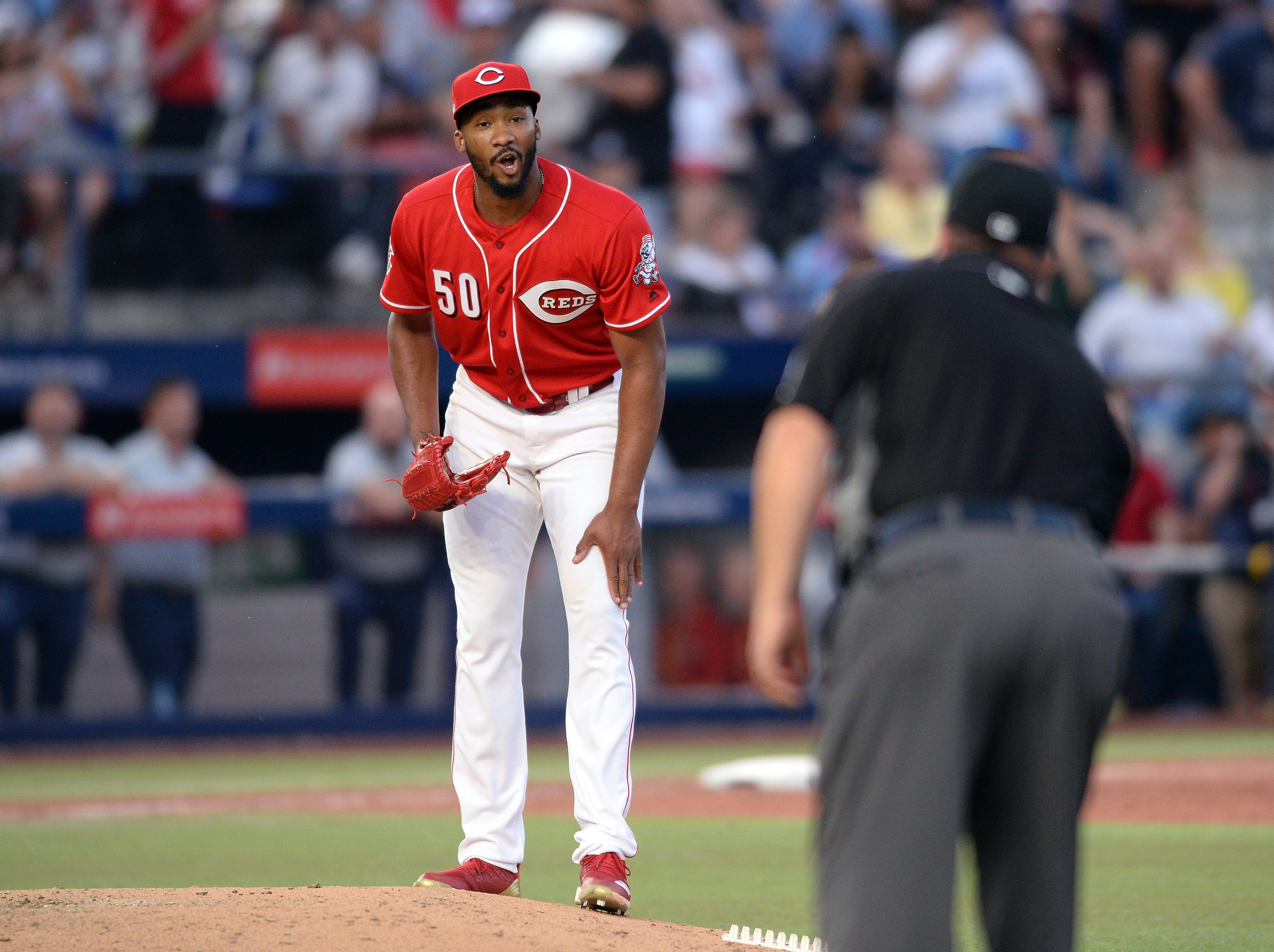 Cincinnati Reds relief pitcher Amir Garrett (50) reacts after a call by first base umpire Sam Holbrook (right) during the sixth inning of the game against the St. Louis Cardinals at Estadio de Beisbol Monterrey.
