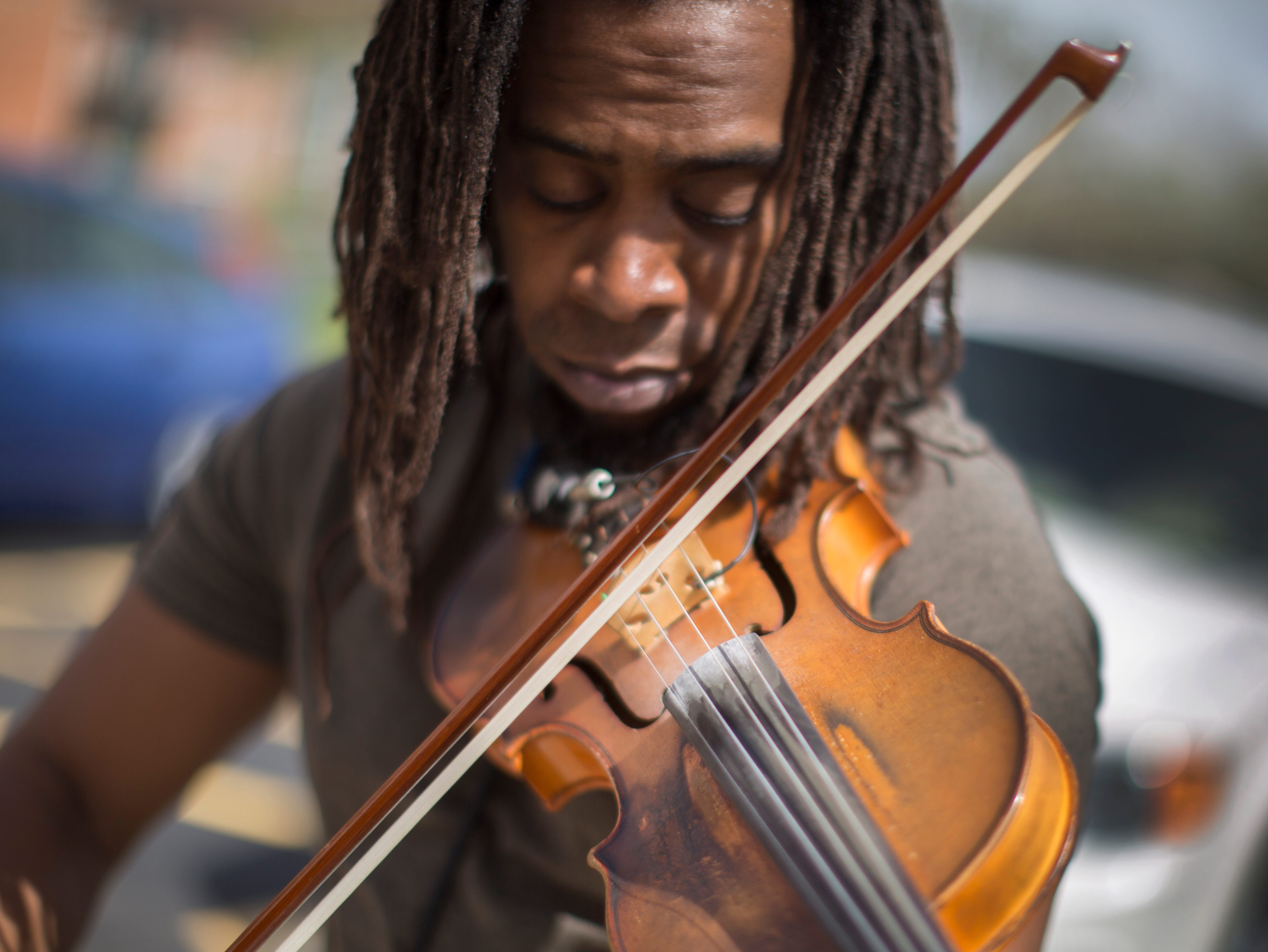 Preston Charles, III, of Silverton, performs his own music on the violin during the healing vigil at St. Paul Village in Madisonville, Saturday, April 13. The Cincinnati chapter of Crime Survivors for Safety and Justice were taking part in the national healing vigil day that gave survivors an opportunity to share their story. Charles, himself a survivor, said, 'The evils in our world can be fought and it's fought from people like you all. Because you actually survive and speak about it. It provides healing and strength to others.'