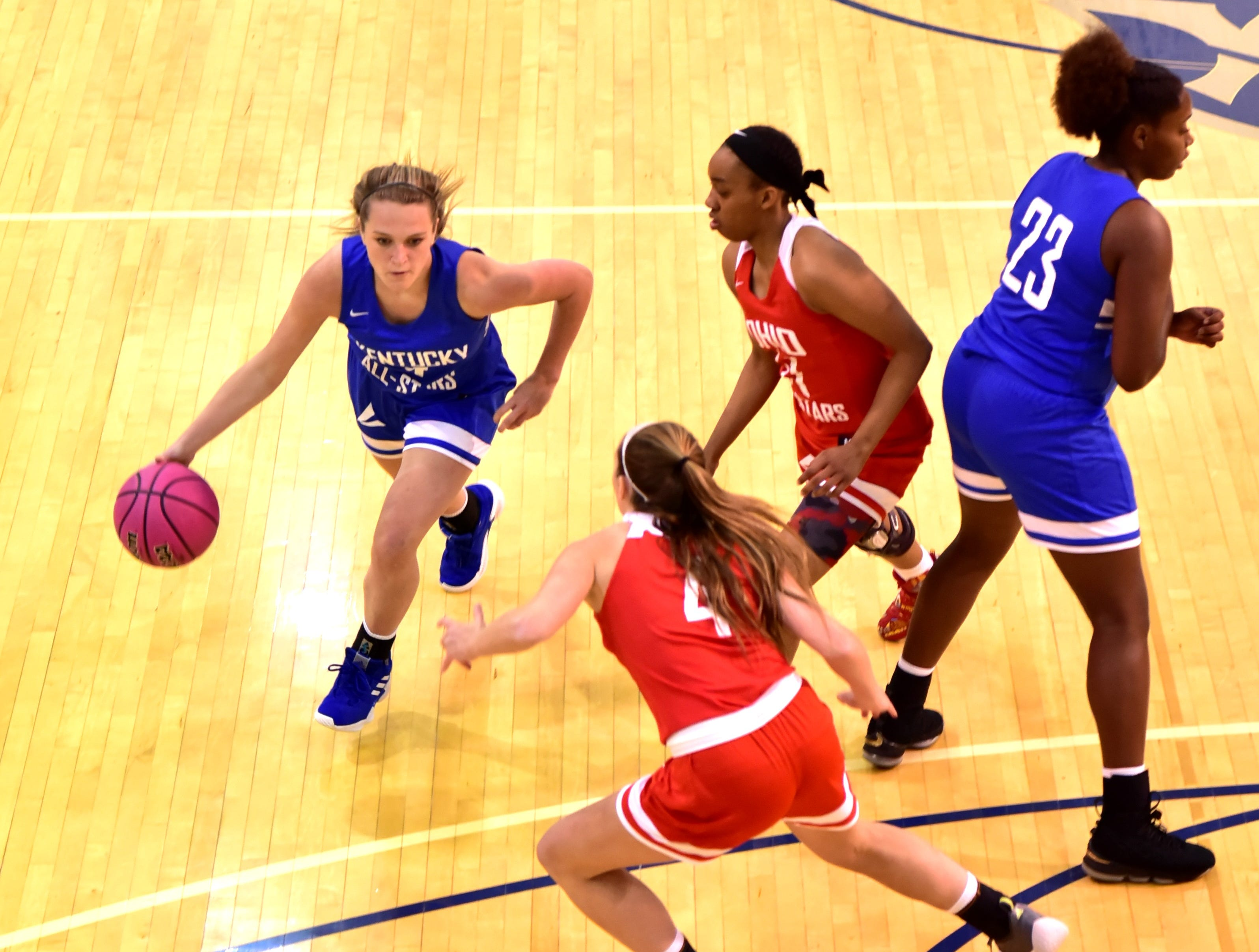 Courtney Hurst (with ball) of Conner dribbles by the Ohio girls team defense for the Kentucky girls team at the 28th Annual Ohio-Kentucky All Star Games played at Thomas More University, April 13, 2019