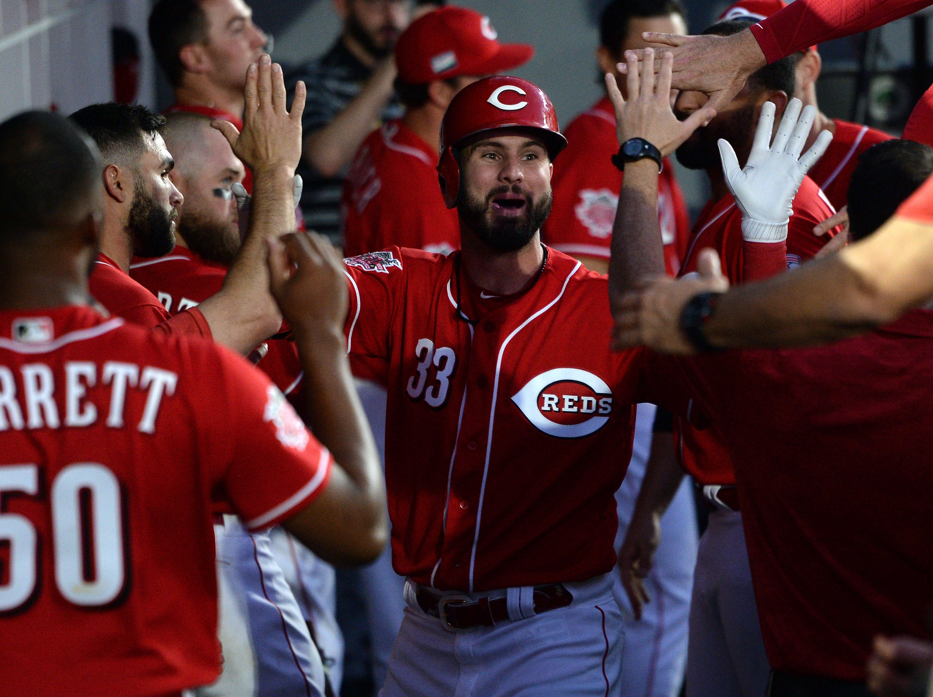 Cincinnati Reds left fielder Jesse Winker (33) is congratulated in the dugout after hitting a home run during the sixth inning against the St. Louis Cardinals at Estadio de Beisbol Monterrey.
