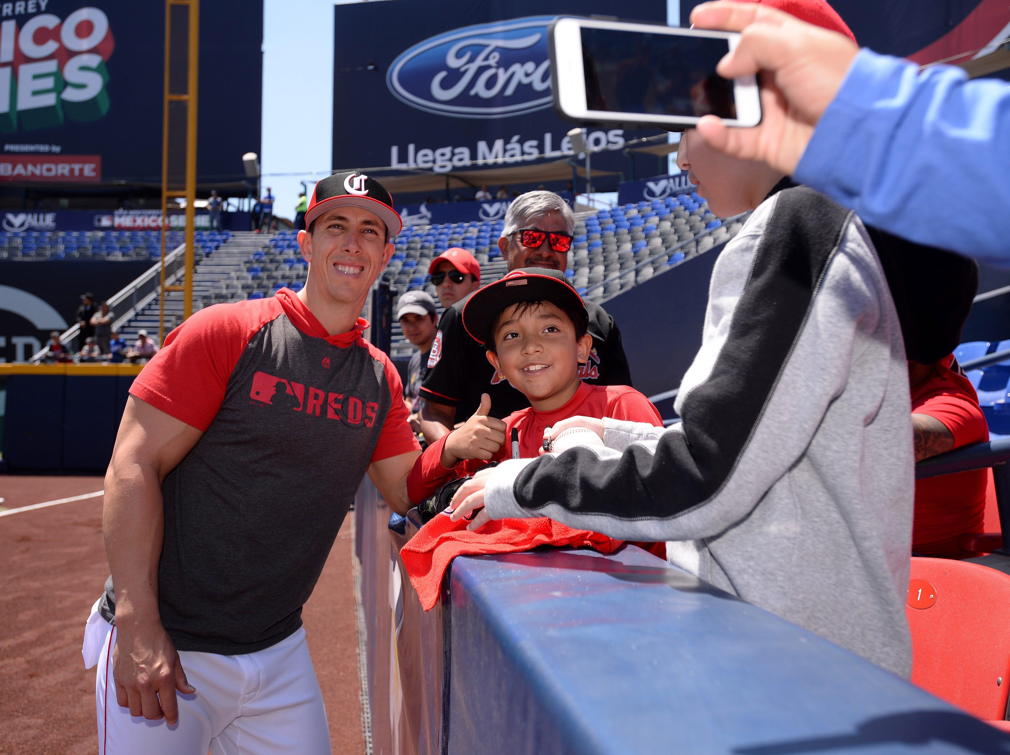 Cincinnati Reds relief pitcher Michael Lorenzen (21) takes a photograph with a fan before the game against the St. Louis Cardinals at Estadio de Beisbol Monterrey.