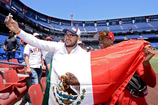 Apr 14, 2019; Monterrey, MEX; Cincinnati Reds relief pitcher Raisel Iglesias (right) takes a picture with a fan holding a Mexican flag before the game against the St. Louis Cardinals at Estadio de Beisbol Monterrey. Mandatory Credit: Orlando Ramirez-USA TODAY Sports