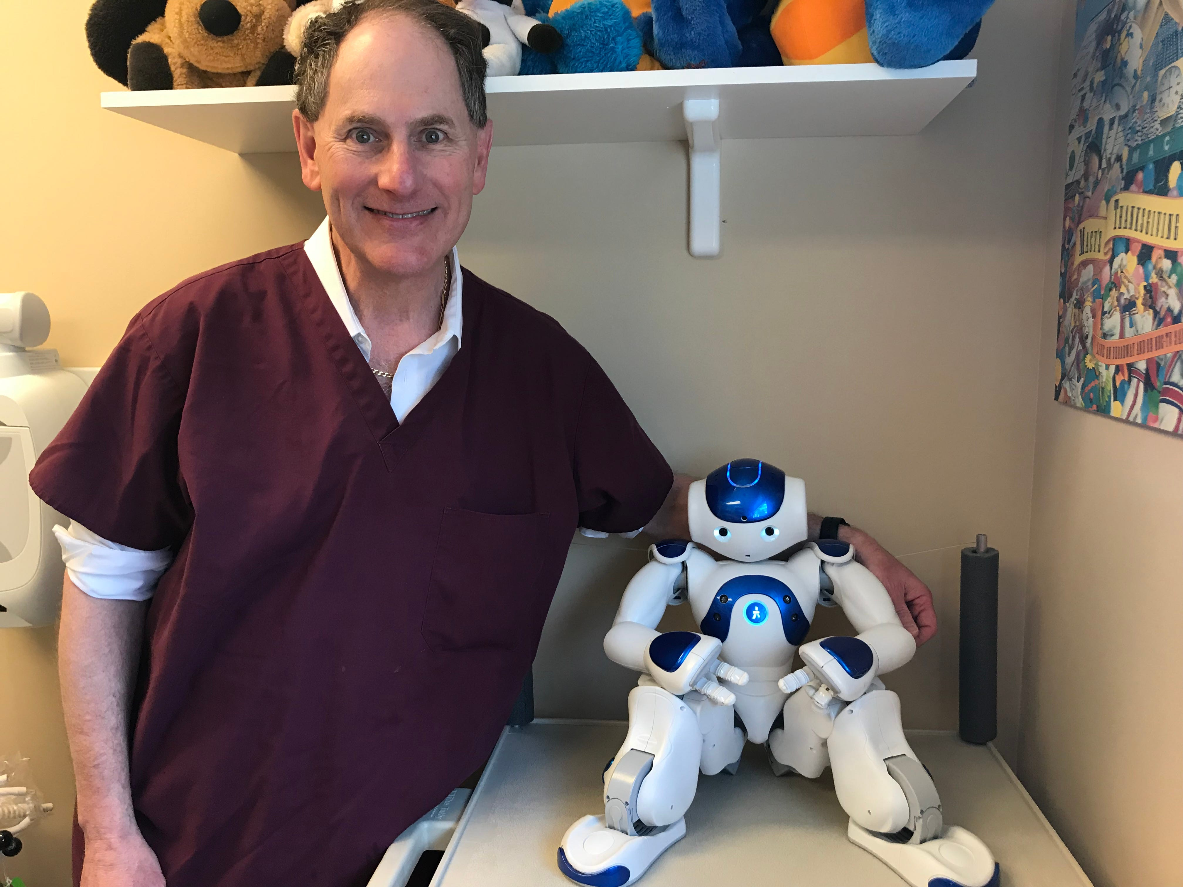 On staff for four years at Olin Dental Group, Medithe robot, here with Dr. Richard Olin, isprogrammed to act asa companion along side children in a dental operatory. Medi is able to speak to children at their level and decrease their concerns, anxietyand fears when they come to the dentist.