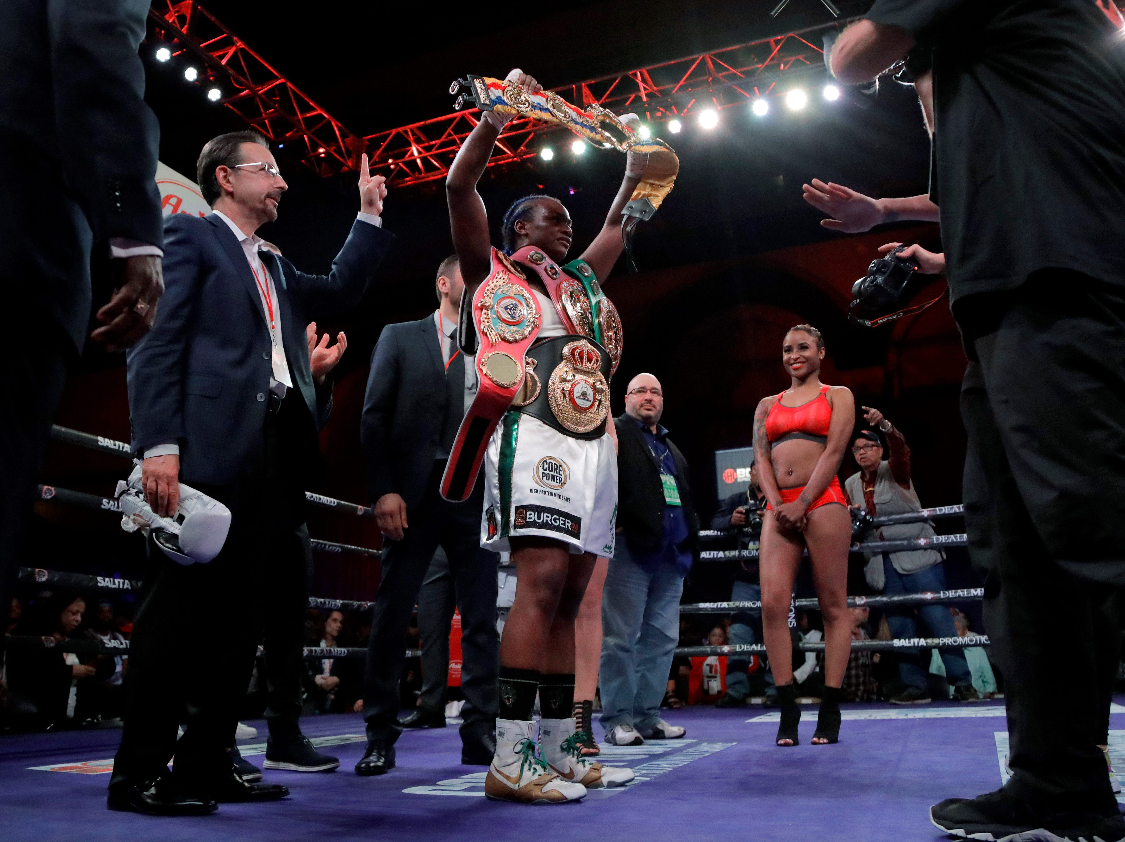 Claressa Shields holds her belts after defeating Christina Hammer during the women's middleweight championship boxing bout Saturday, April 13, 2019, in Atlantic City, N.J. Shields won by unanimous decision.
