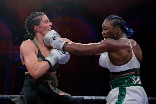 Claressa Shields, right, lands a left to Christina Hammer during the 10th round of a women's middleweight championship boxing bout Saturday, April 13, 2019, in Atlantic City, N.J. Shields won by unanimous decision.