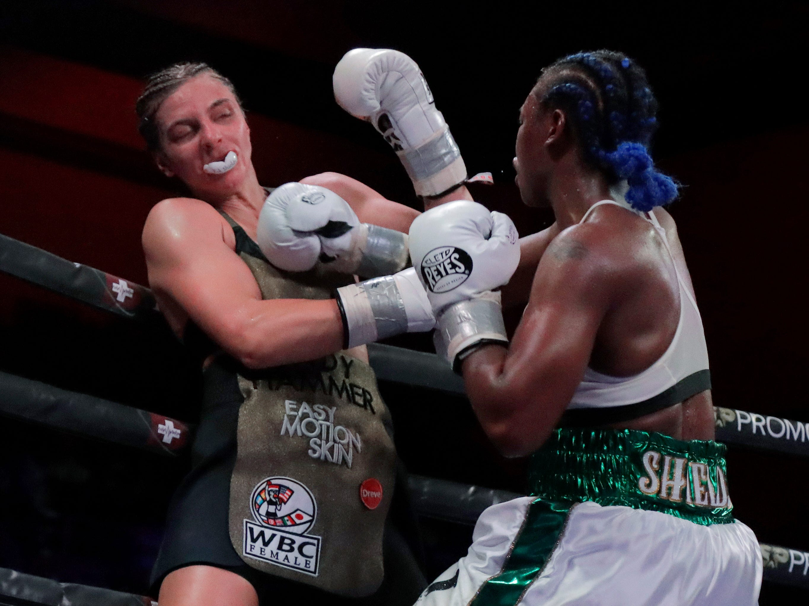 Claressa Shields, right, punches the mouthpiece out of Christina Hammer's mouth during the eighth round of the women's middleweight championship boxing bout Saturday, April 13, 2019, in Atlantic City, N.J. Shields won by unanimous decision.
