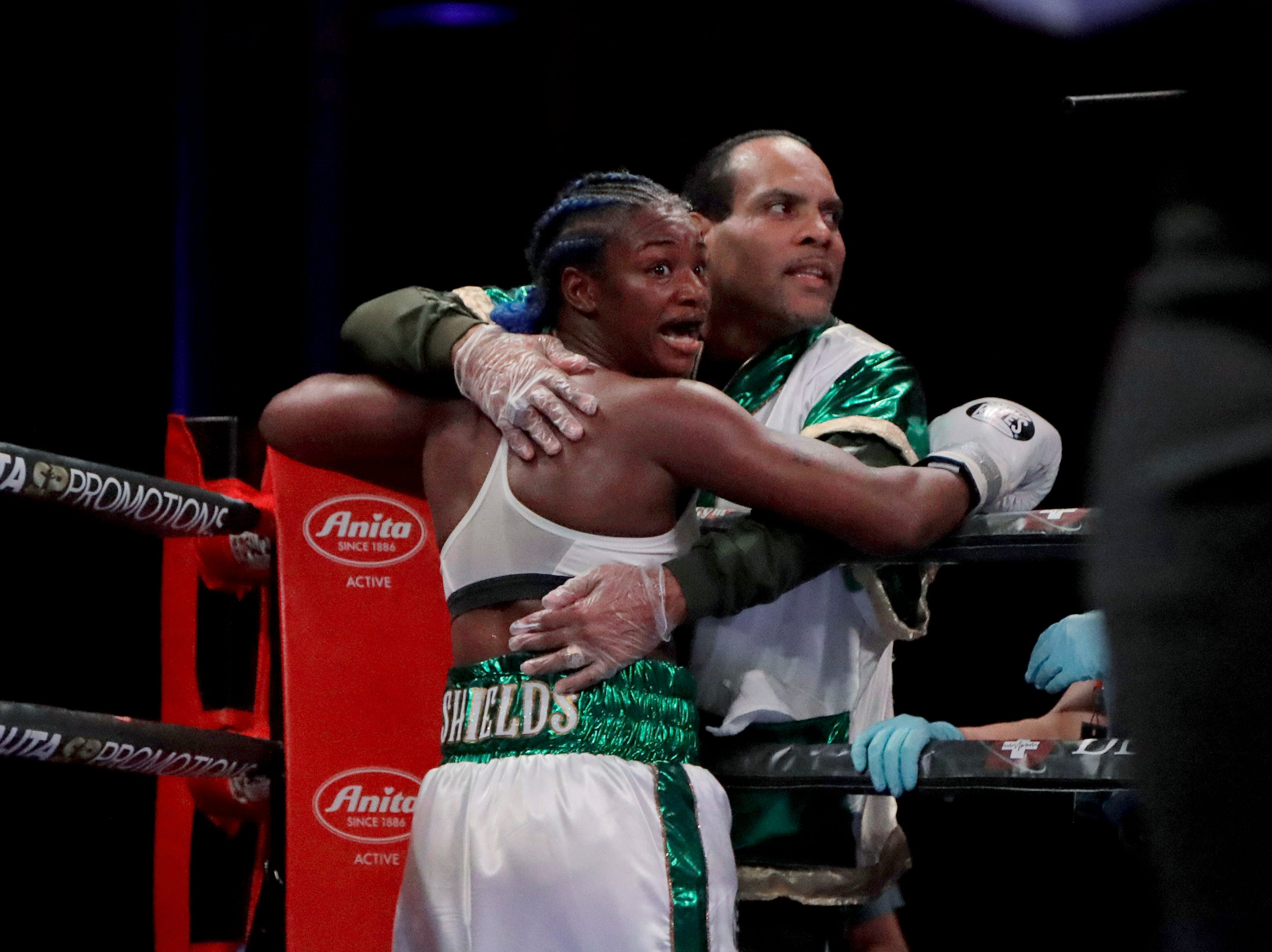 Claressa Shields, left, hugs a member of her team at the end of the eighth round against Christina Hammer during the women's middleweight title boxing bout Saturday, April 13, 2019, in Atlantic City, N.J. Shields, who won by unanimous decision, believed she had seen a white towel thrown on the ring and thought she had won. Shields went on to win by unanimous decision.