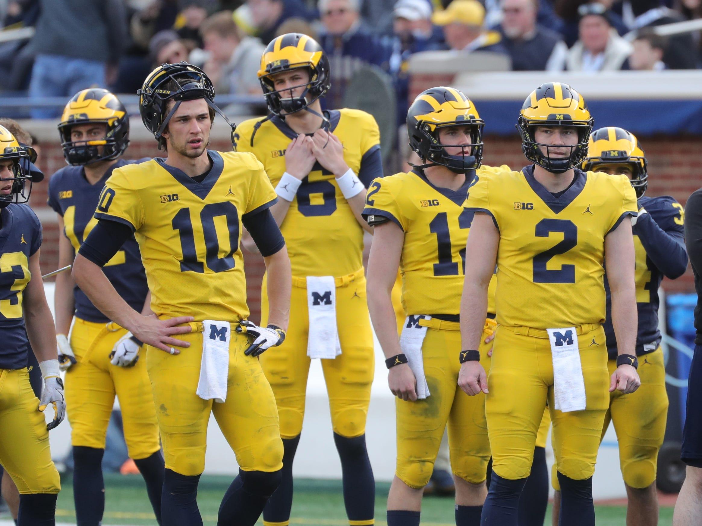 Michigan quarterbacks Shea Patterson (2) and Dylan McCaffrey (10) watch the spring game Saturday, April 13, 2019 at Michigan Stadium in Ann Arbor.