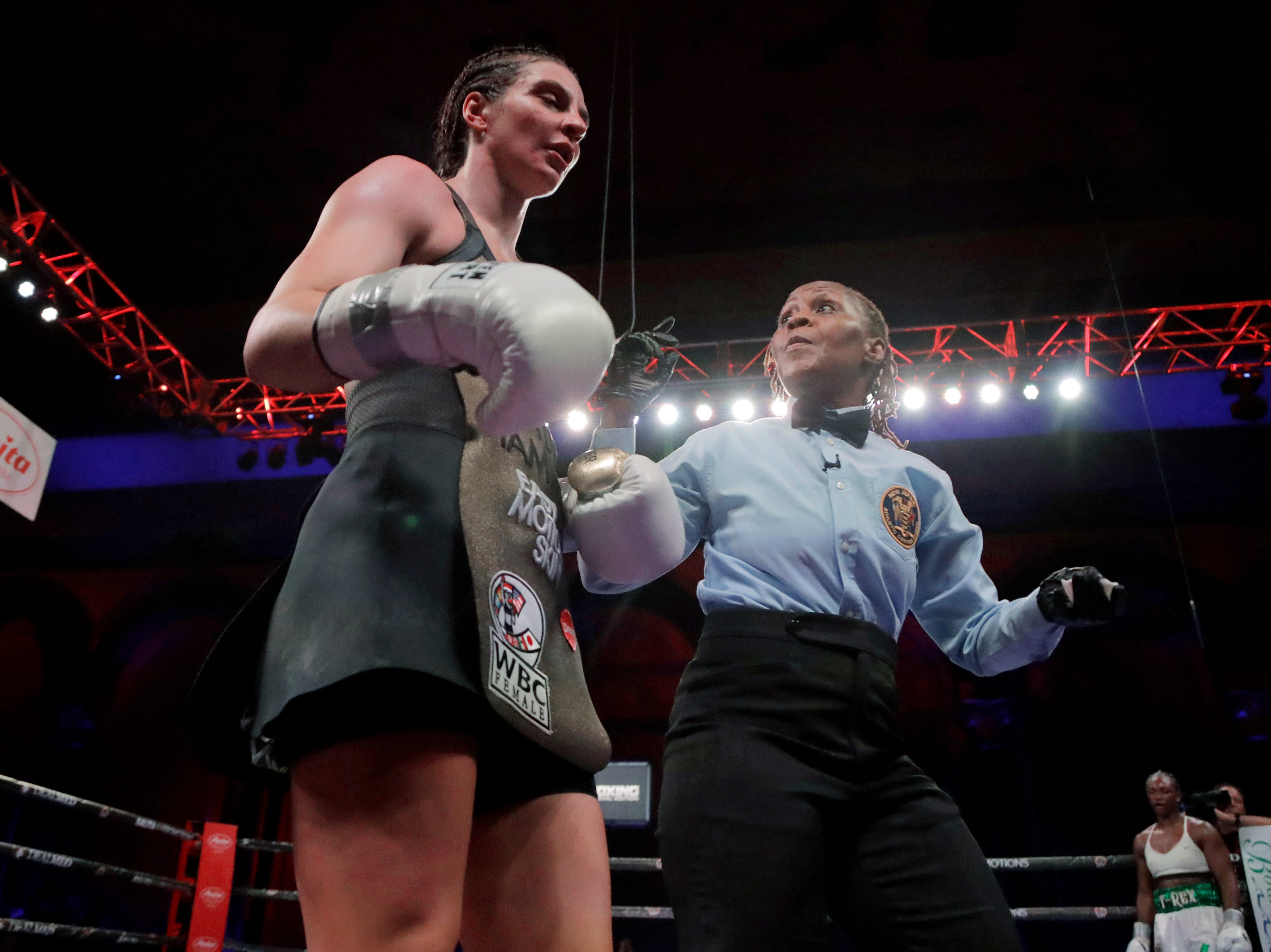 Referee Sparkle Lee, right, talks to Christina Hammer after Hammer lost her mouthpiece during the eighth round of the women's middleweight championship boxing bout against Claressa Shields, Saturday, April 13, 2019, in Atlantic City, N.J. Shields won by unanimous decision.