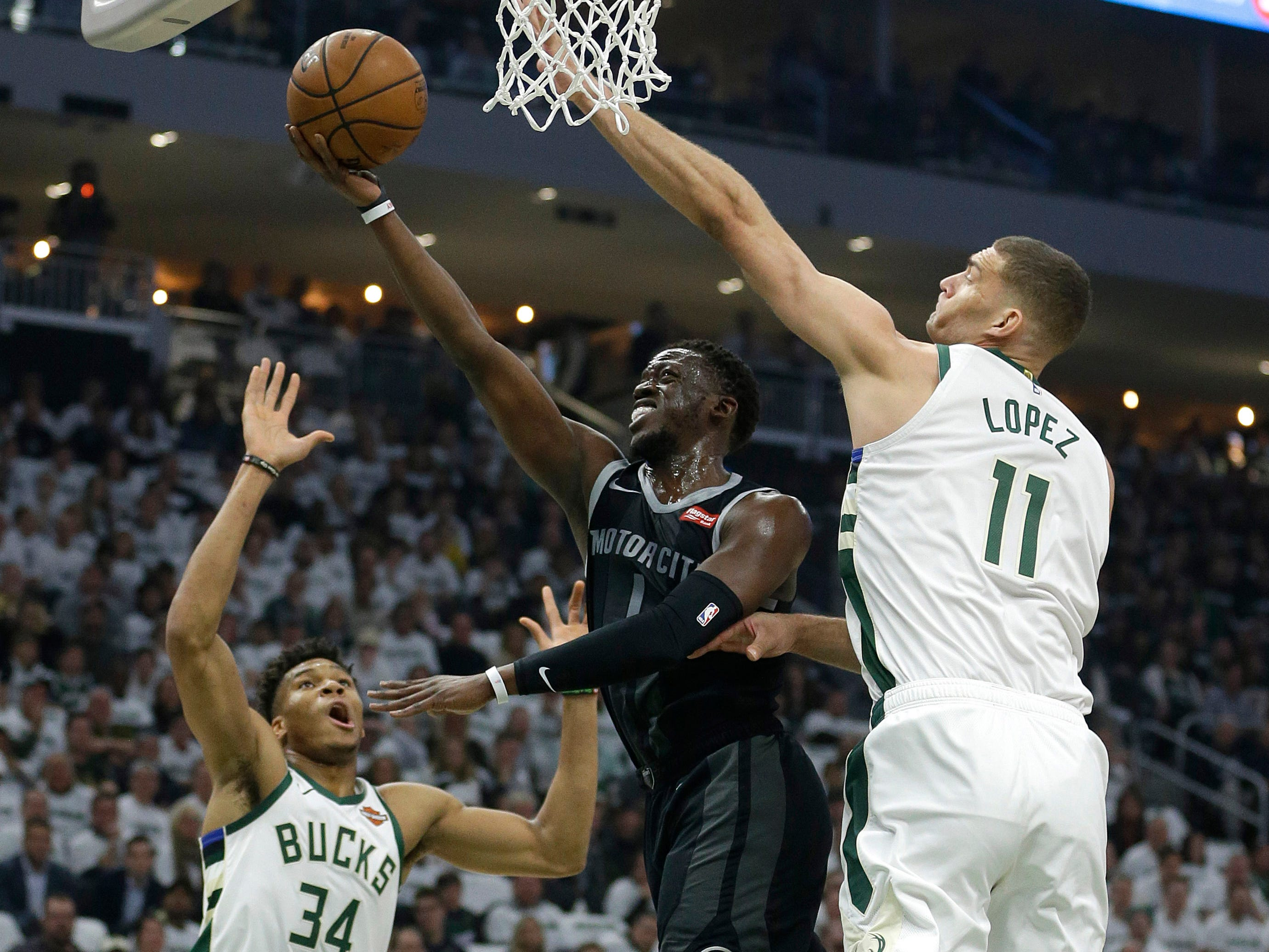 Detroit Pistons' Reggie Jackson shoots between Milwaukee Bucks' Brook Lopez (11) and Giannis Antetokounmpo (34) during the first half of Game 1 on Sunday, April 14, 2019, in Milwaukee.
