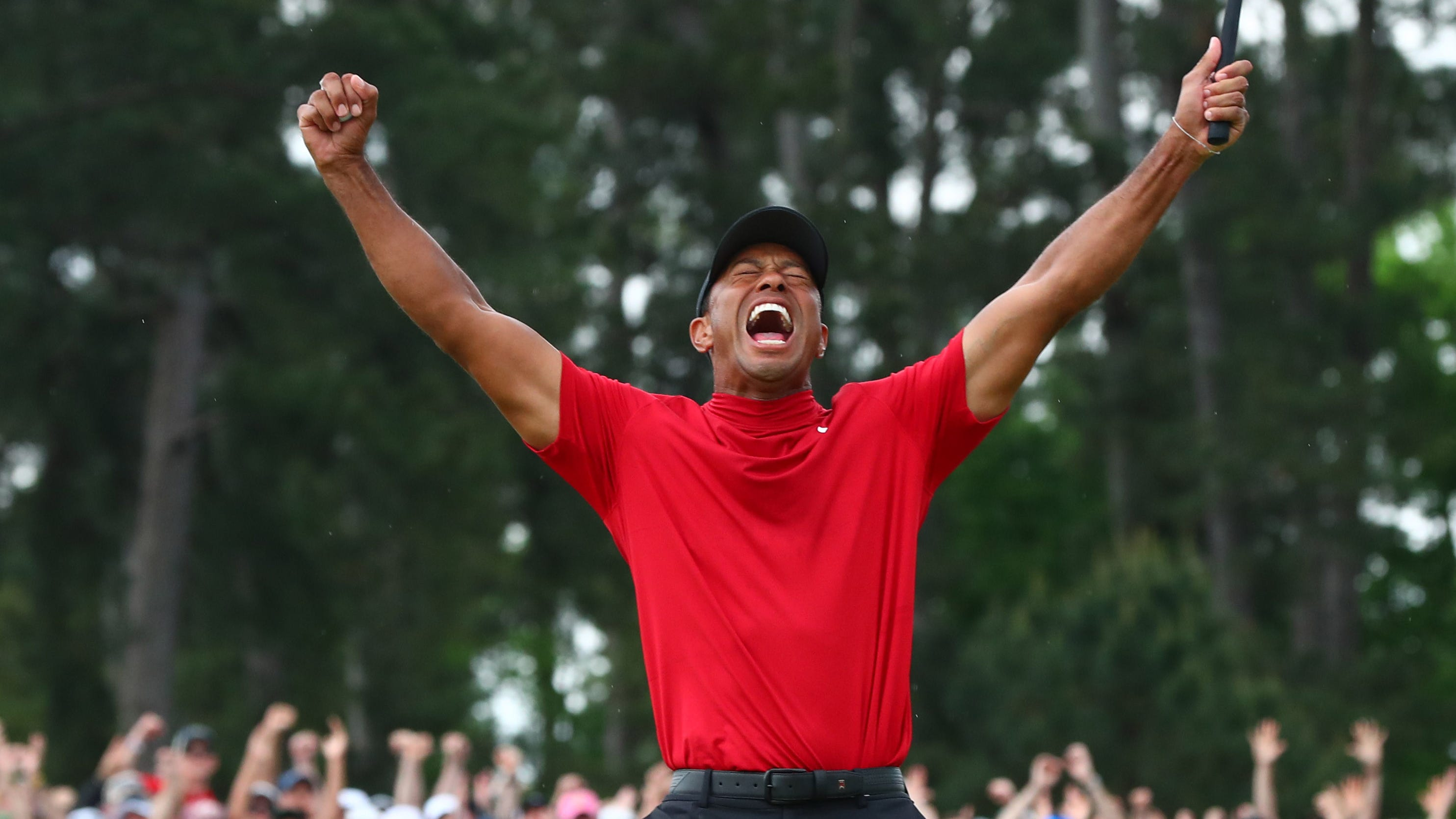 Tiger Woods celebrates after making a putt on the 18th green to win The Masters golf tournament at Augusta National Golf Club, April 14, 2019.